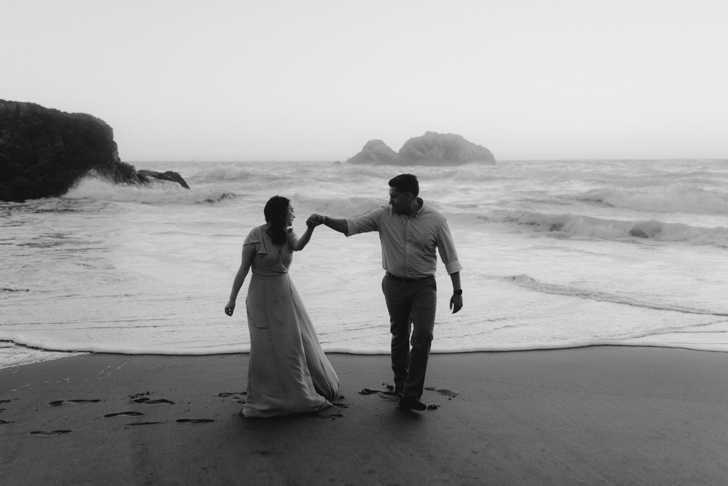 Sutro Baths Engagement Session, photo of couple walking away from an ocean wave