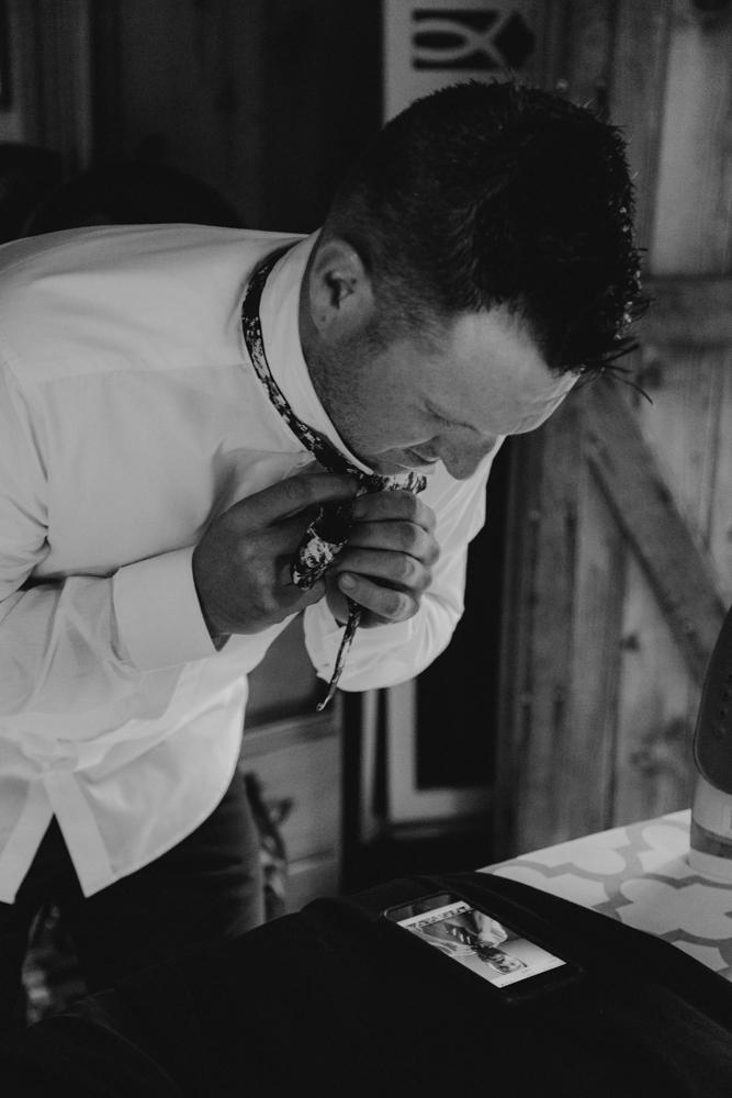 Twenty Mile House Wedding Photographer, groom putting on his bowtie photo