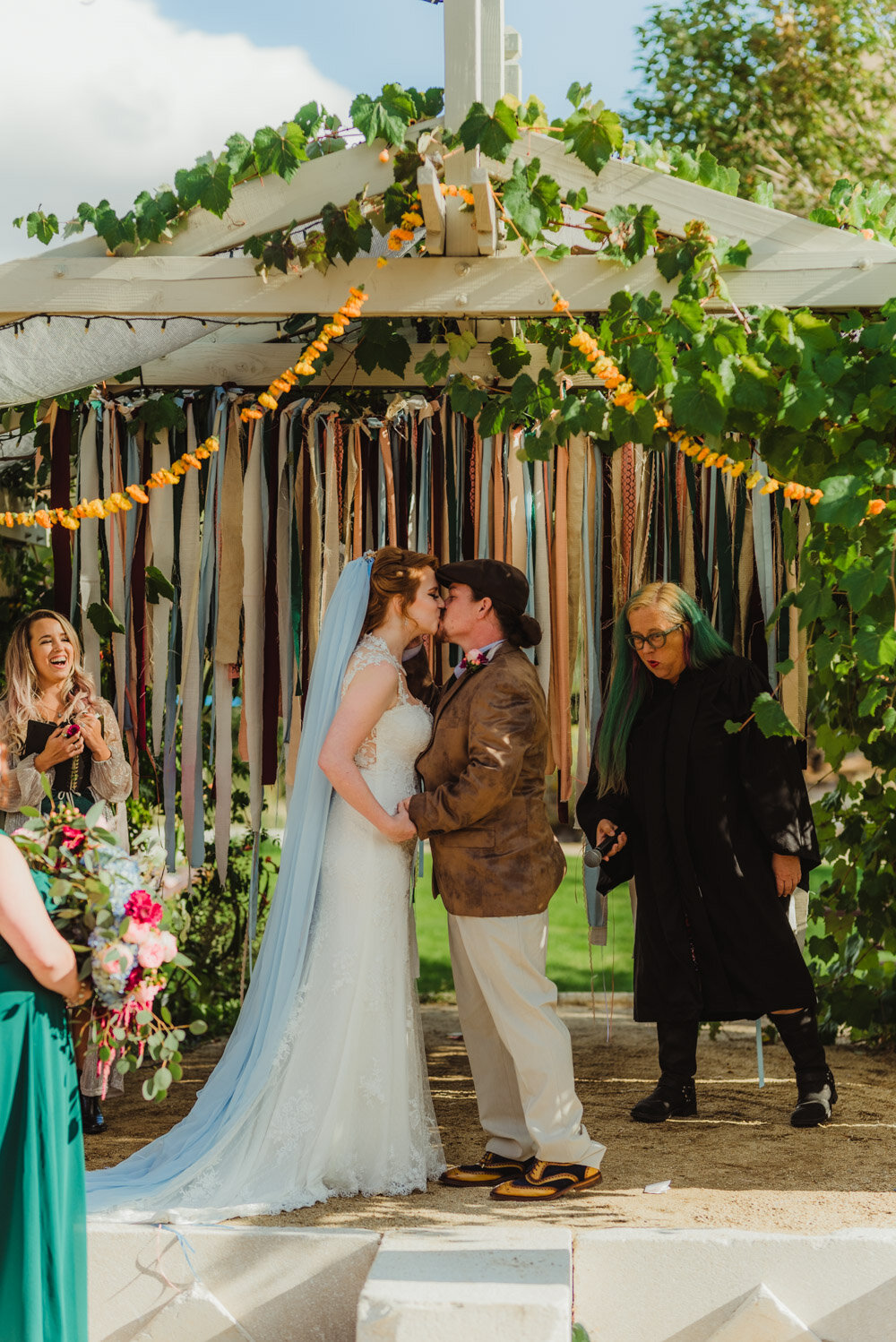 River School Farm Wedding, couple kissing with a ribbon background
