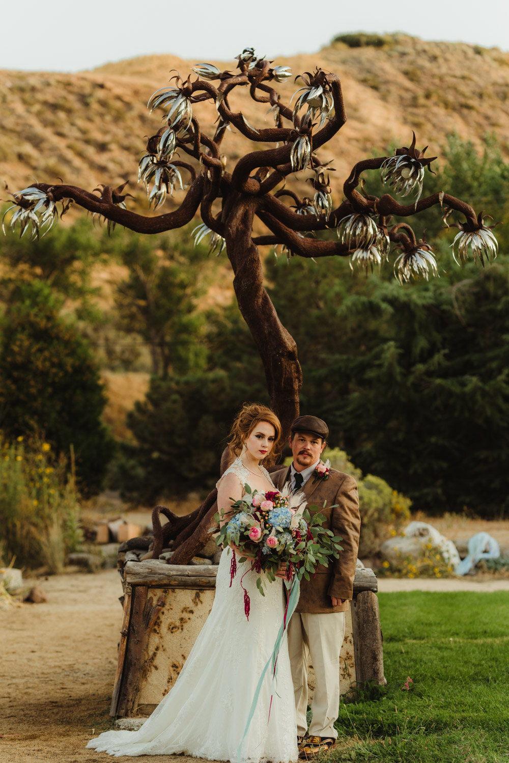 River School Farm Wedding, photo of couple in front of a burning man like sculpture