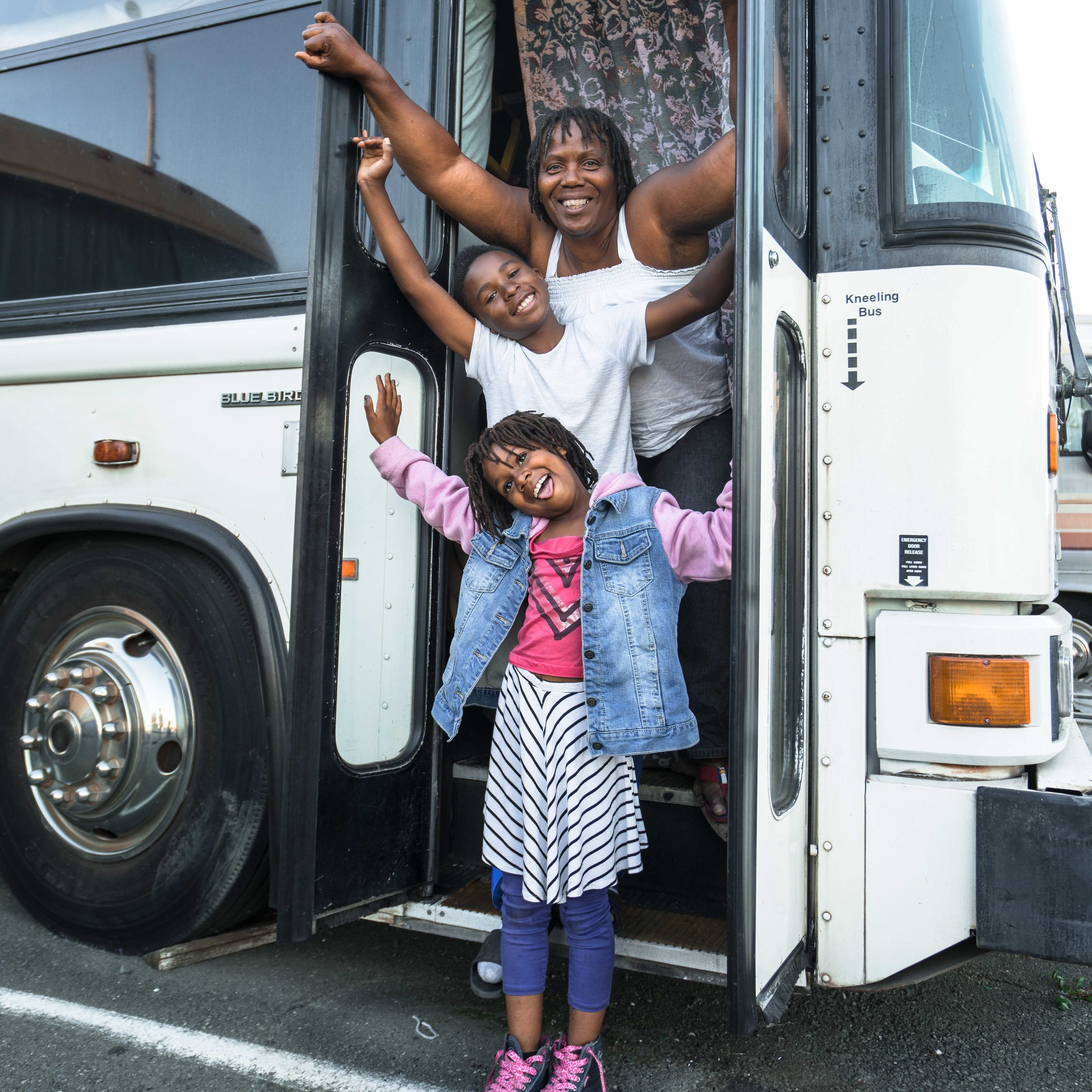 Constance and her children, David and Miracle, looking forward to turning their bus into a home.