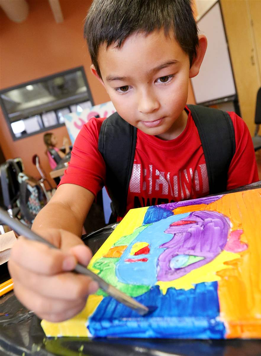 Nicolas Bossany, 9, works on his Picasso-inspired self-portrait Thursday at the Menomonie school district's summer school art camp at Menomonie High School. This class asked students what makes good art and challenged them to convey messages in their own art.