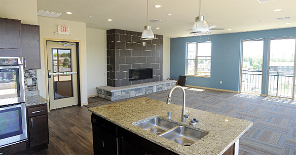Among the amenities for Lumberyard 1505 renters is a community room with full kitchen and fireplace. There is a fitness room and a rooftop patio area attached to the community room.  Photo by Mark Justesen