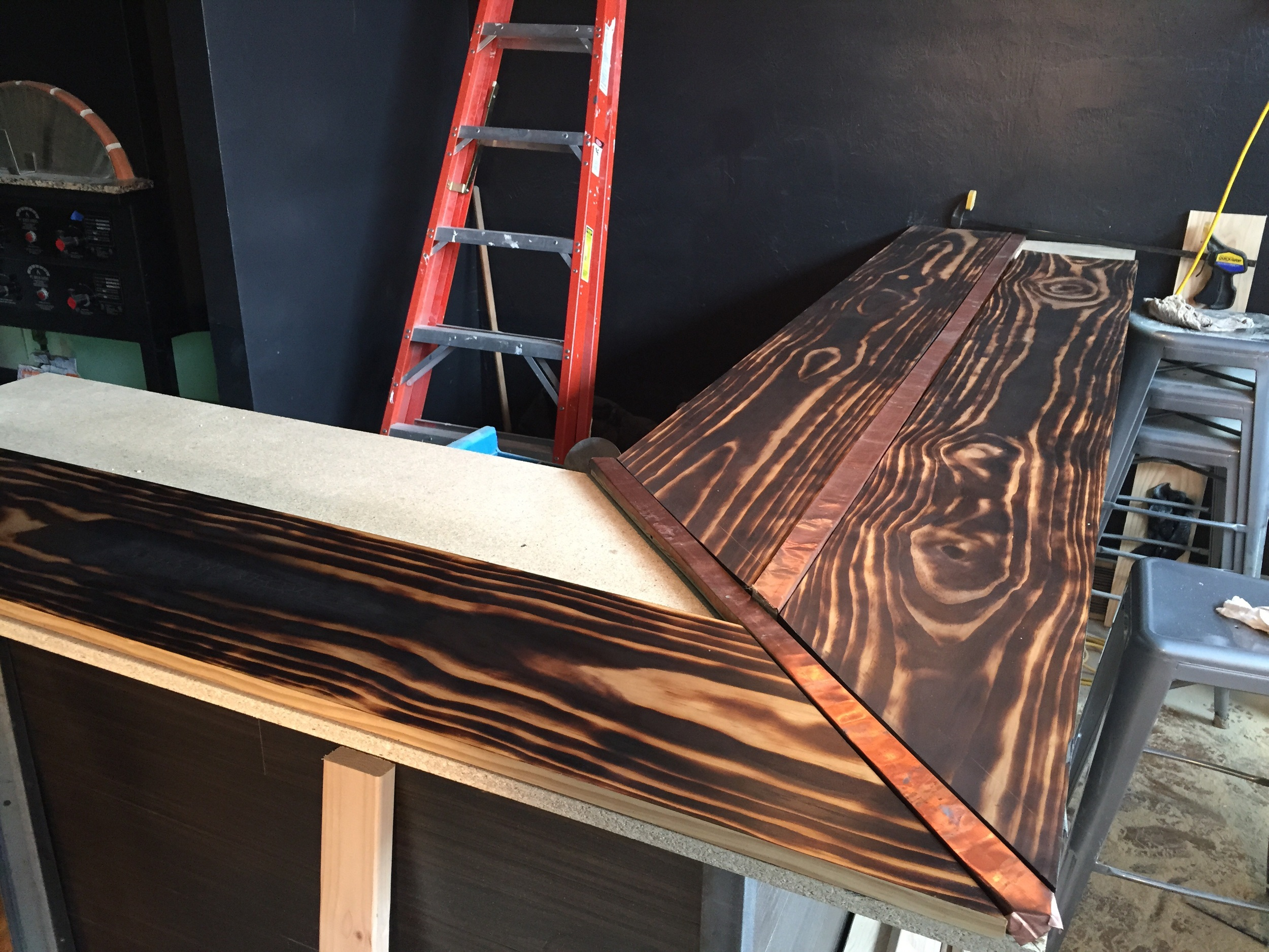 The bar is mid-construction here.  The wood for this bar was stained a natural color to let the burnt grain pattern stay visible down the length of it.