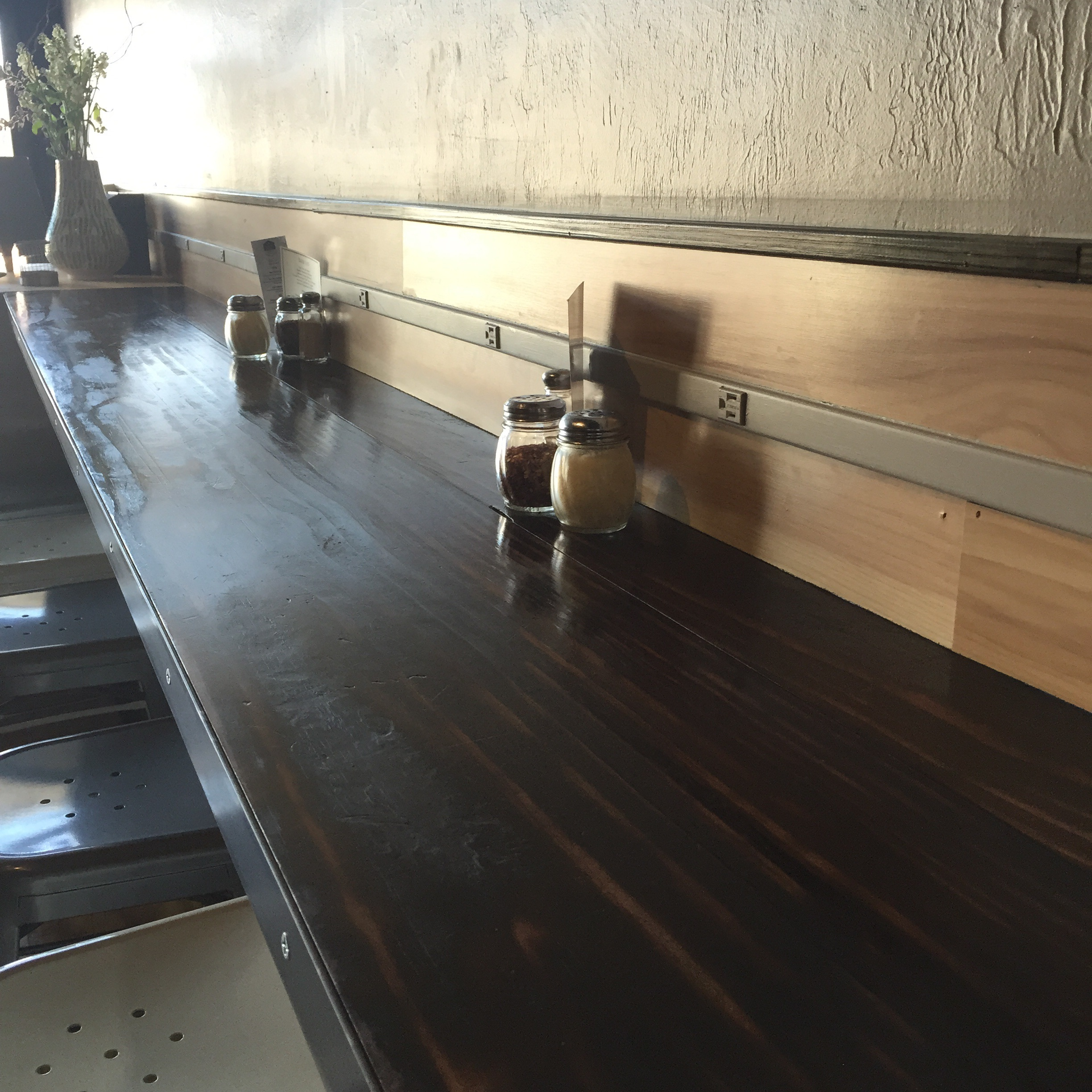 """The """"smart bar"""" was stained in a deeper mahogany tone. Scorched areas are visible with the reflections from the light."""