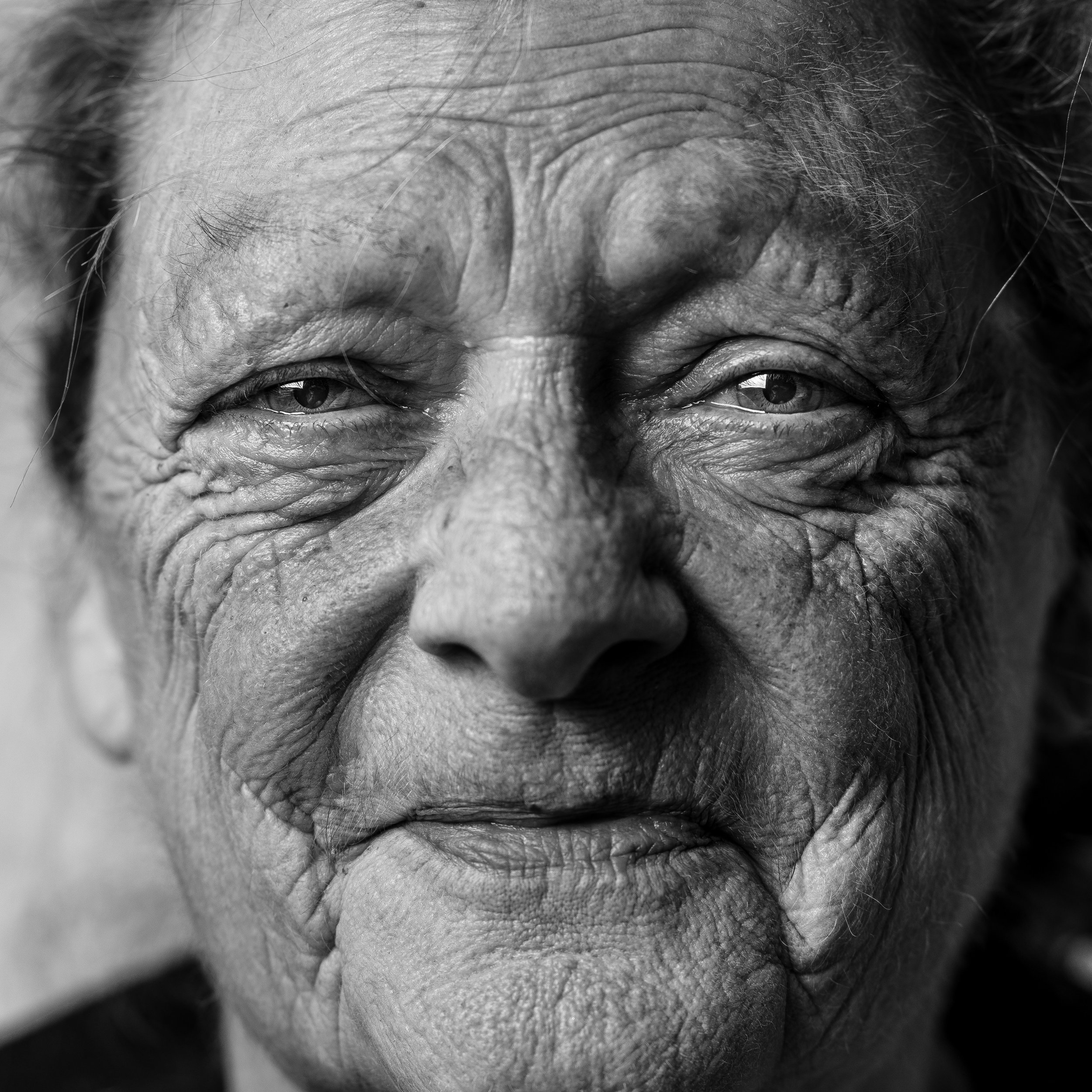 "This is a photograph by @angelsvicente from UnSplash. About it, she writes: ""This is a portrait of my mum, trying to show through her facial expression the warmth in her character as well as all the experiences that she has lived in her life. I did the portrait from the living room in the home she has been living for most of her life."""