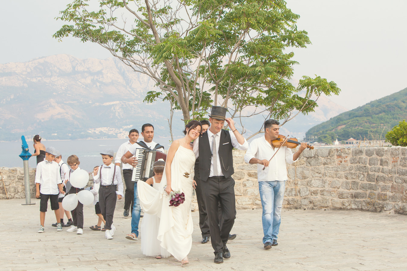 One of a set of images taken at Vanessa and Thor's destination Wedding in the beautiful Porto Montenegro. Bride and Groom are followed by a local band.  Wedding Photography By Matt Porteous
