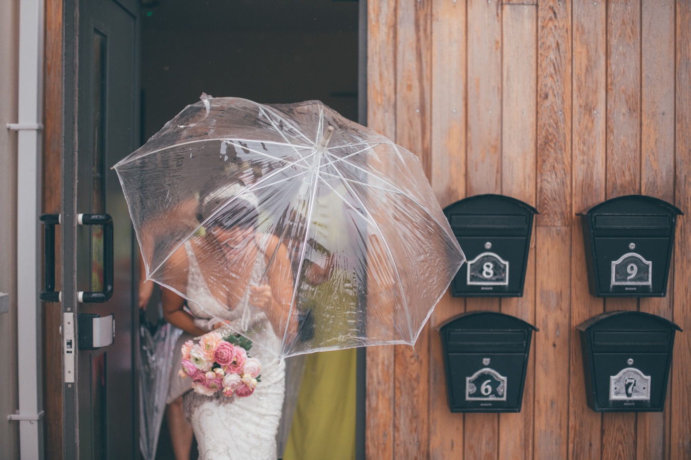 One of a set of images taken at this Destination Wedding of Jo and Steve, Jersey The Channel islands. Bride in the rain on her way to the wedding. Wedding Photography By Matt Porteous & Max Burnett.