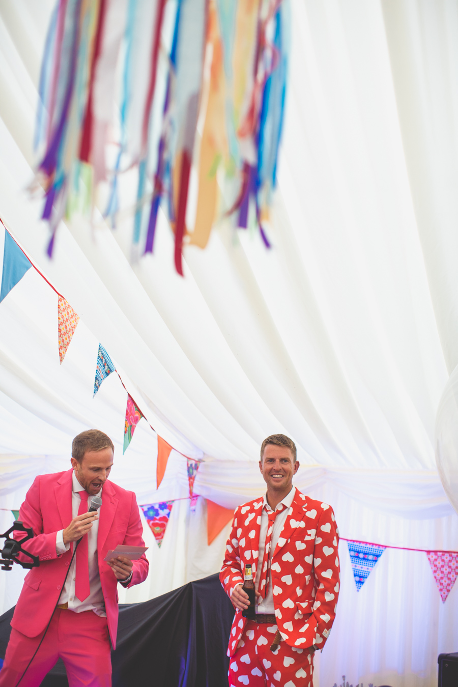 One of a set of images taken at this Destination Wedding of Jo and Steve, Jersey The Channel islands.Mr. Lover Opposuit Groom listens to best man's speech.Photography By Matt Porteous & Max Burnett.