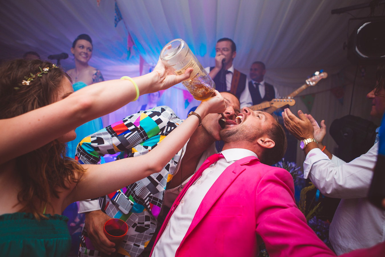 One of a set of images taken at this Destination Wedding of Jo and Steve, Jersey The Channel islands. Wedding party drinking in pink and checkered opposuits.Photography By Matt Porteous & Max Burnett.