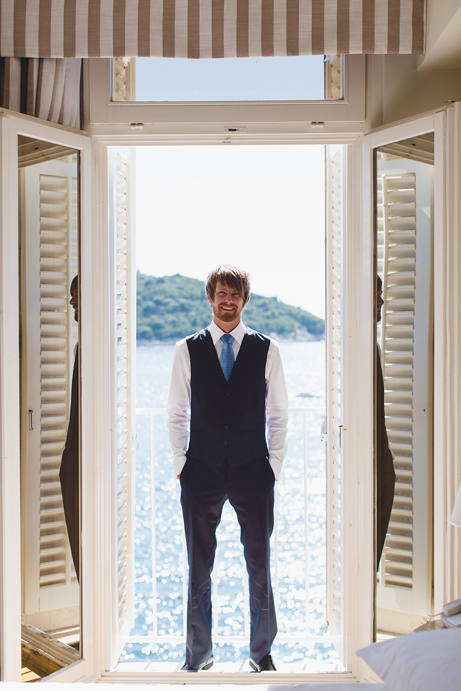 One of a set of images taken at this chic destination Wedding of Jenna & Nick. The stylish old town of Dubrovnik, Croatia.  The Groom stands with the sea in the background.Photography by Matt Porteous