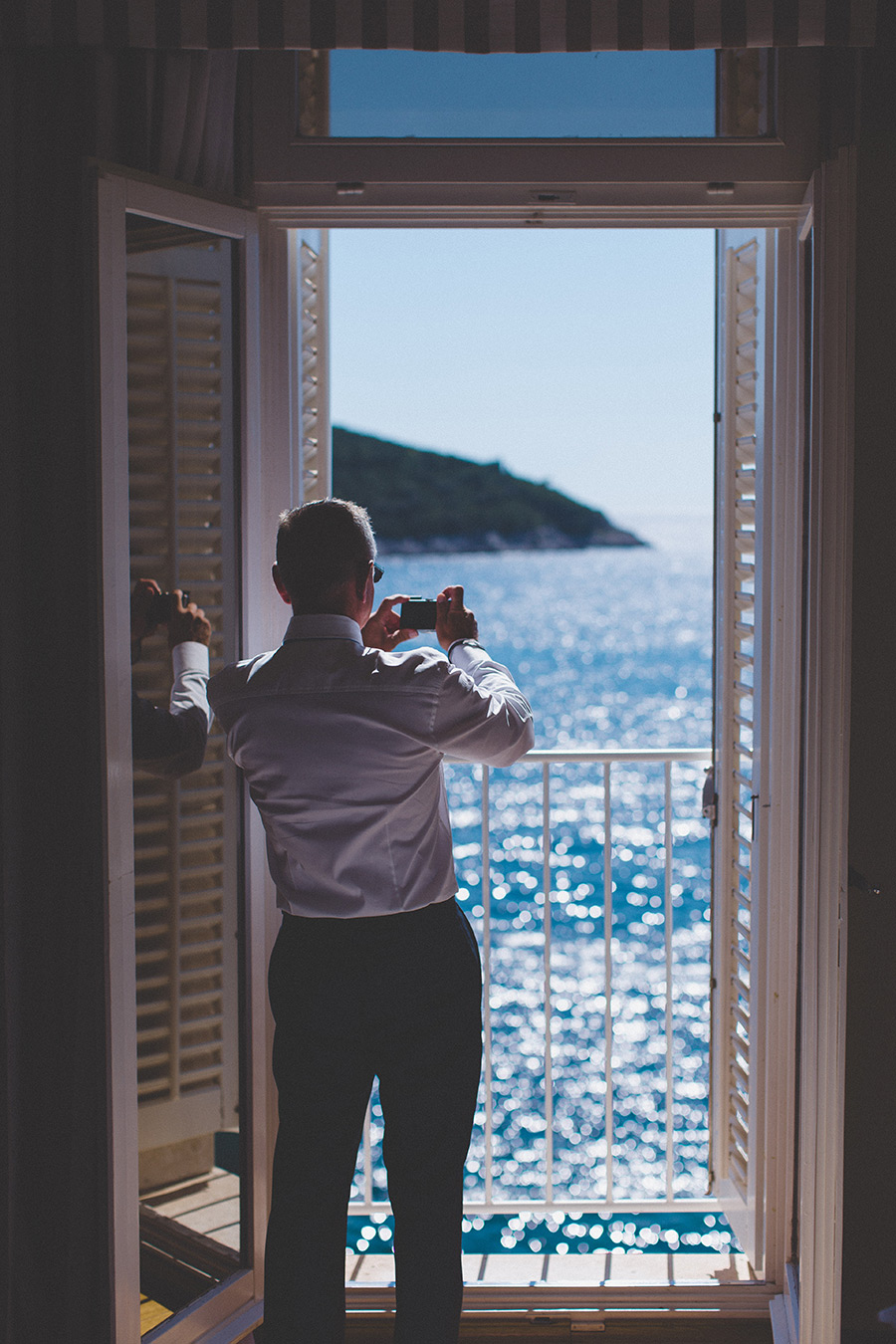 One of a set of images taken at this chic destination Wedding of Jenna & Nick. The stylish old town of Dubrovnik, Croatia.  The bright sun hitting the blue ocean.  Photography by Matt Porteous