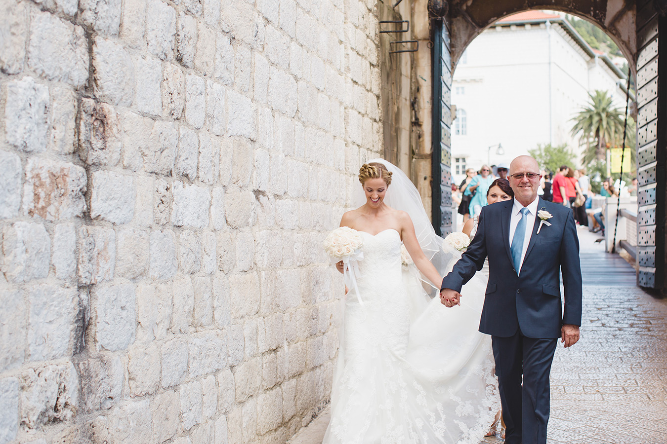 One of a set of images taken at this chic destination Wedding of Jenna & Nick. The stylish old town of Dubrovnik, Croatia.  The father of the Bride walks with his daughter.Photography by Matt Porteous