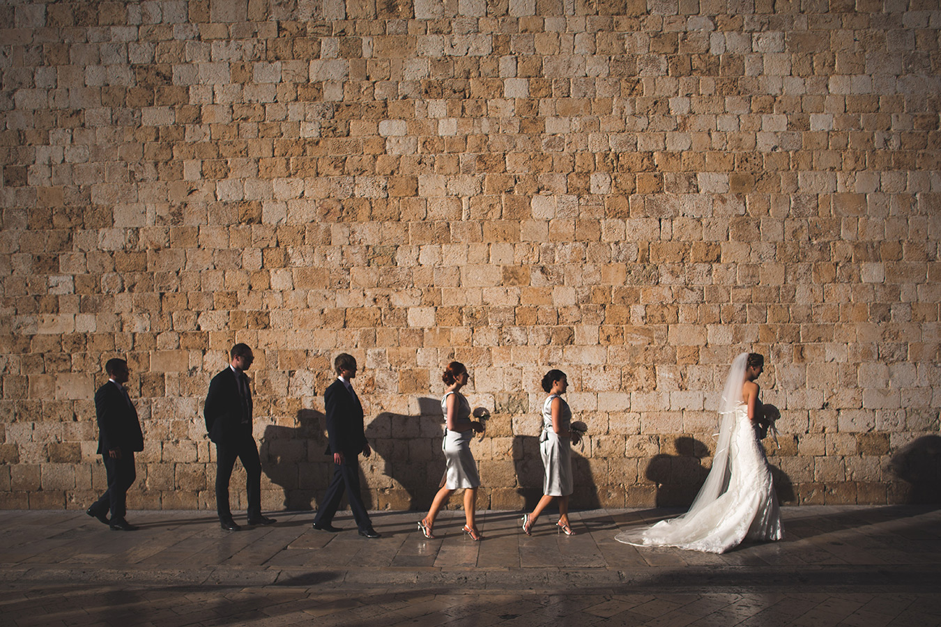 One of a set of images taken at this chic destination Wedding of Jenna & Nick. The stylish old town of Dubrovnik, Croatia.  The Bride and Bridesmaids walk down the street. Photography by Matt Porteous