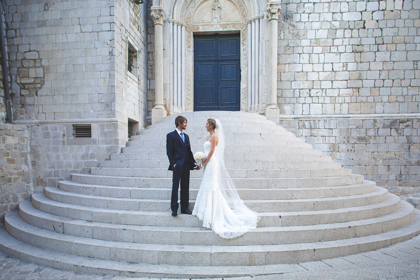 One of a set of images taken at this chic destination Wedding of Jenna & Nick. The stylish old town of Dubrovnik, Croatia.  The couple pose on the steps.  Photography by Matt Porteous