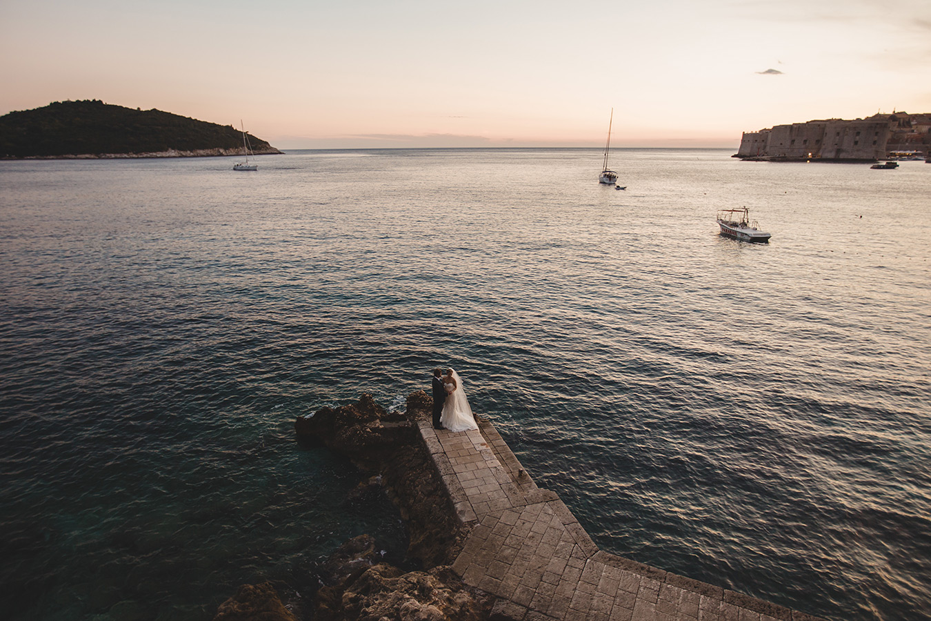 One of a set of images taken at this chic destination Wedding of Jenna & Nick. The stylish old town of Dubrovnik, Croatia.  The couple sit together by the water.  Photography by Matt Porteous