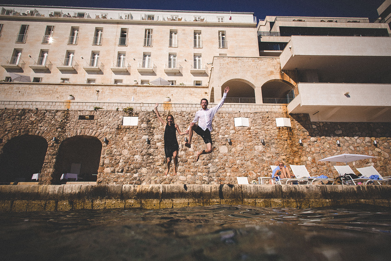 One of a set of images taken at this chic destination Wedding of Jenna & Nick. The stylish old town of Dubrovnik, Croatia.  The couple jump into the sea.  Photography by Matt Porteous