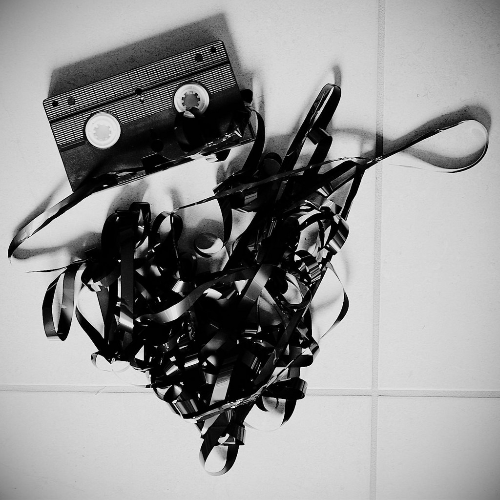 """A VHS cassette, with internal magnetic tape unfurled:""""Projet 365 - 054/365.Old tape"""" - Nicolas Buffler. Via  Flickr . License:  CC BY 2.0"""