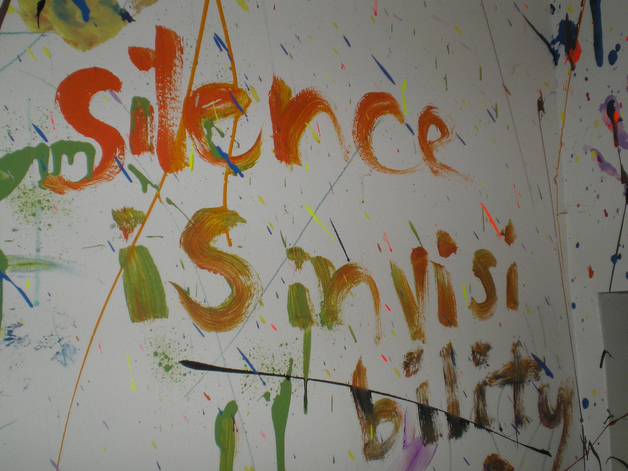 'Silence is Invisibility', by Melina Vanni-González. Source:    Flickr.    White wall, flecked with paint, with graffiti in orange and red stating 'silence is invisibility'. (CC BY-SA 2.0.)