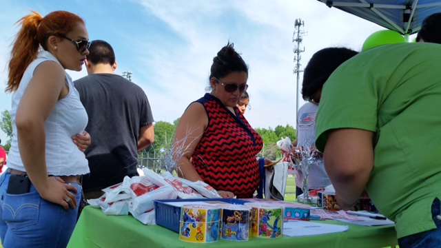 Copa Telemundo Soccer Tournament attendees learning about and getting goodie bags from Family Dental of Richmond