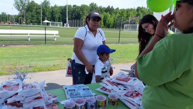 Mom with her son learning about Family Dental of Richmond at the Copa Telemundo Soccer Tournament