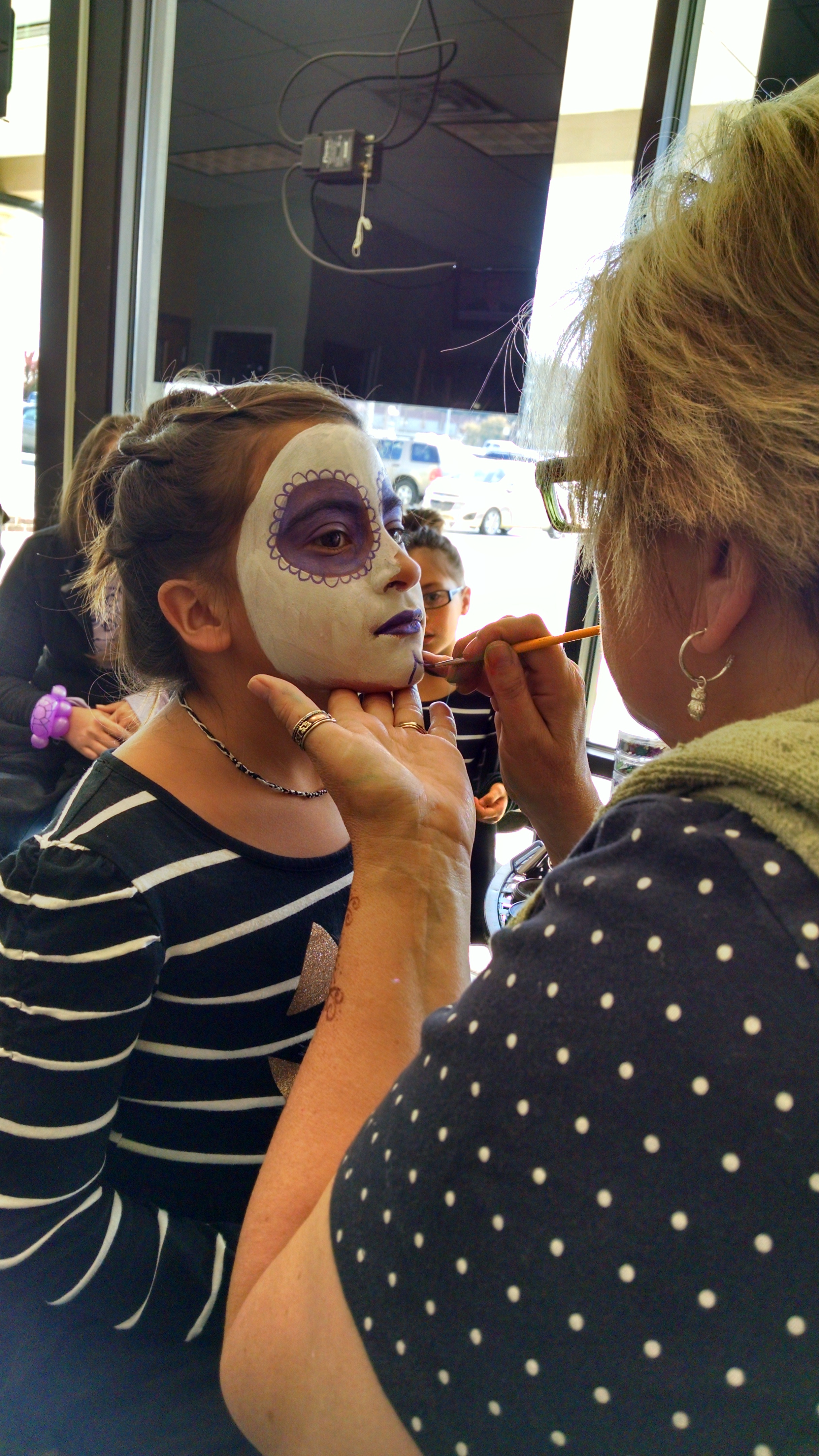 Melanie Thoman getting her face painted by Donna Grentz from Mimzy's Face Painting