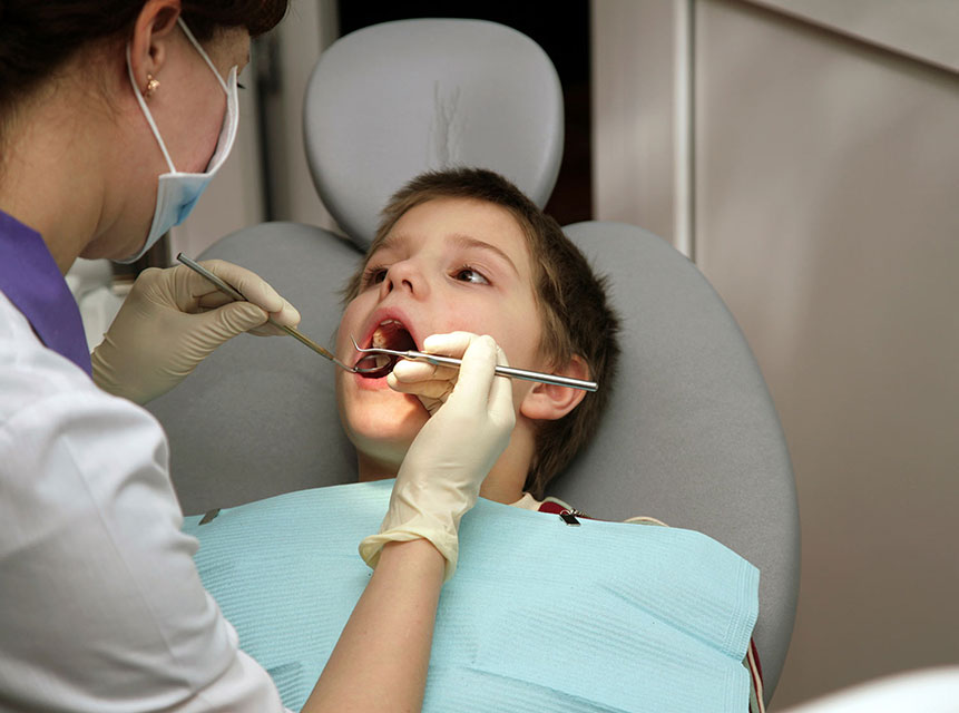 Boy getting his teeth cleaned by a dentist