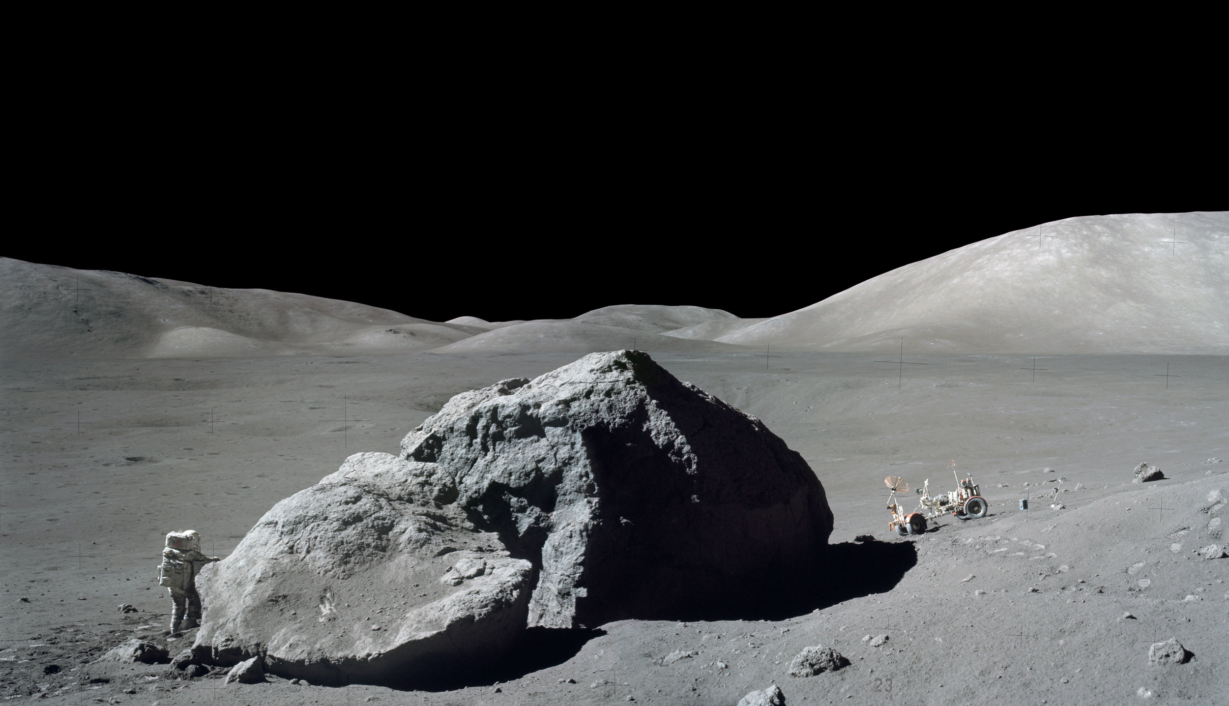 Smithsonian Website Caption: Dec. 13, 1972, scientist-astronaut Harrison H. Schmitt is photographed standing next to a huge, split lunar boulder during the third Apollo 17 extravehicular activity (EVA) at the Taurus-Littrow landing site. The Lunar Roving Vehicle (LRV), which transported Schmitt and Eugene A. Cernan to this extravehicular station from their Lunar Module (LM), is seen in the background. The mosaic is made from two frames from Apollo 17 Hasselblad magazine 140. The two frames were photographed by Cernan.