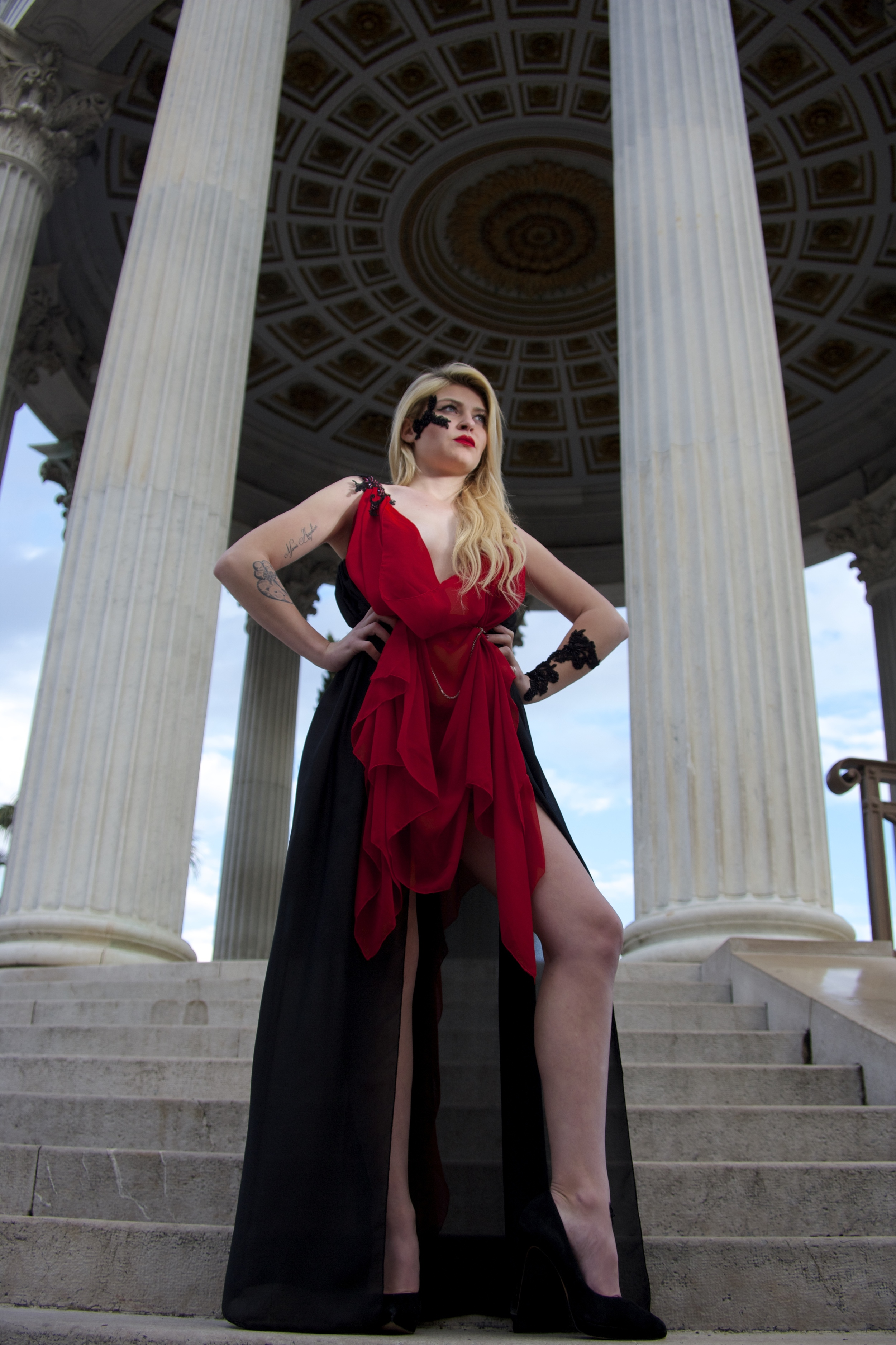 Blond Godess standing in the arches of a roman temple Haute couture