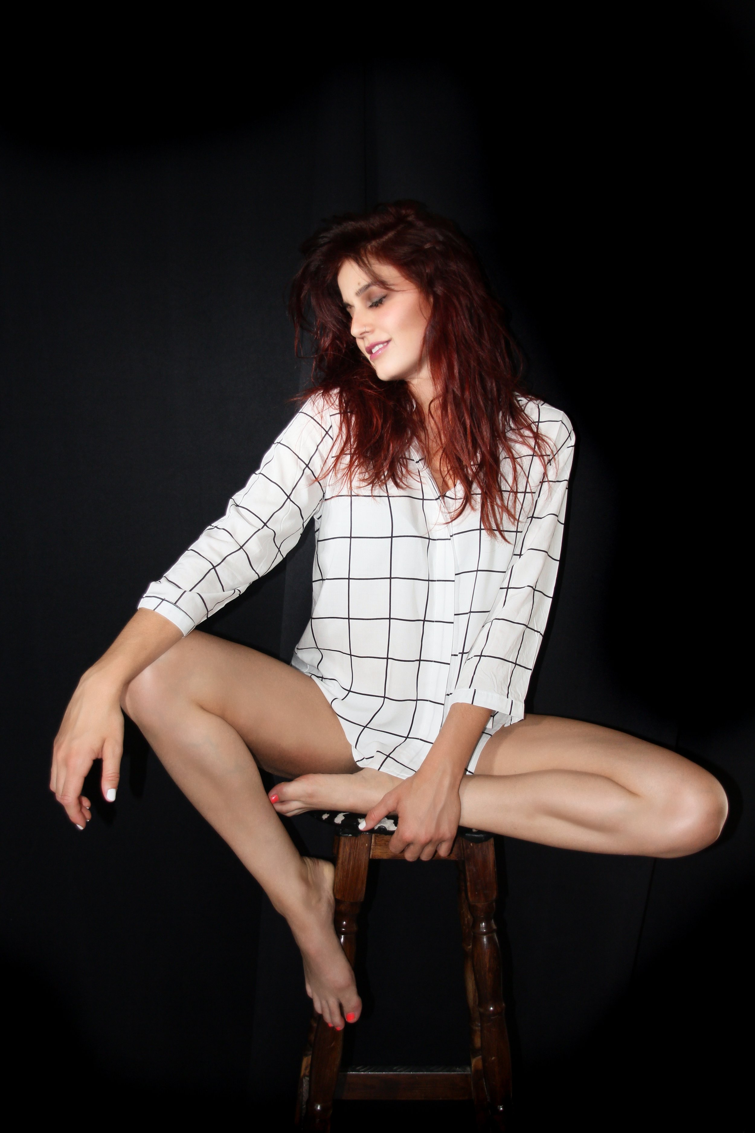 red head model sitting on a bar stool wearing nothing but a man's shirt in front of a black backdrop
