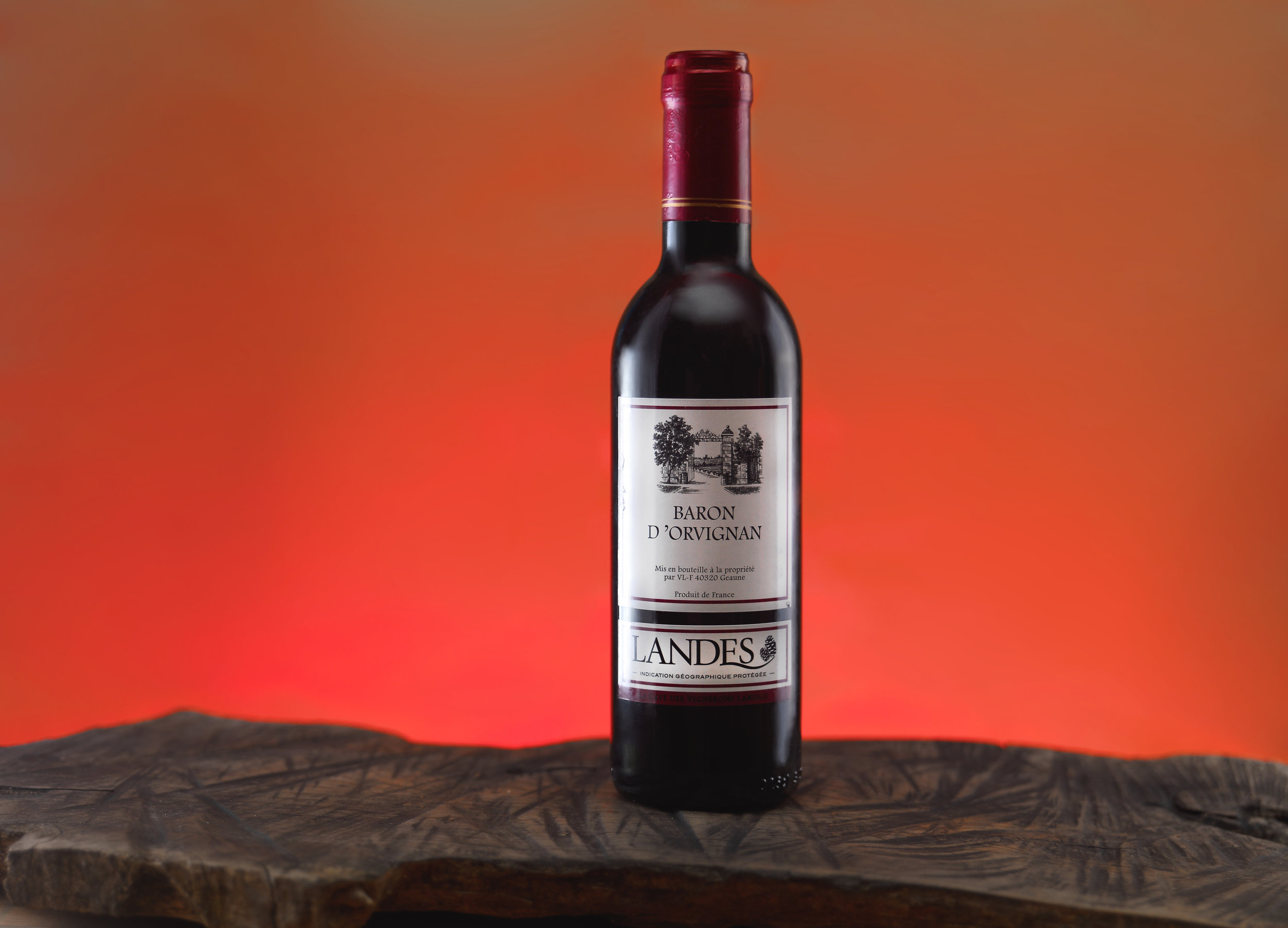 Shot of a bottle of red wine over a red gradient backdrop