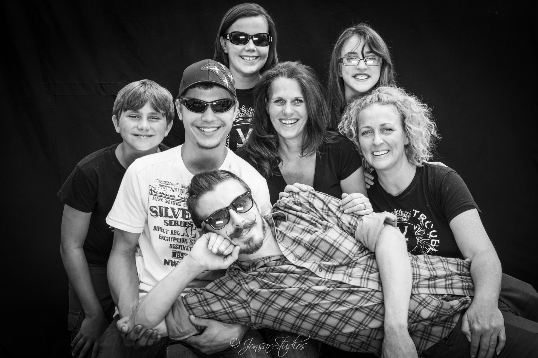 Family group with reclining man photographed on black background