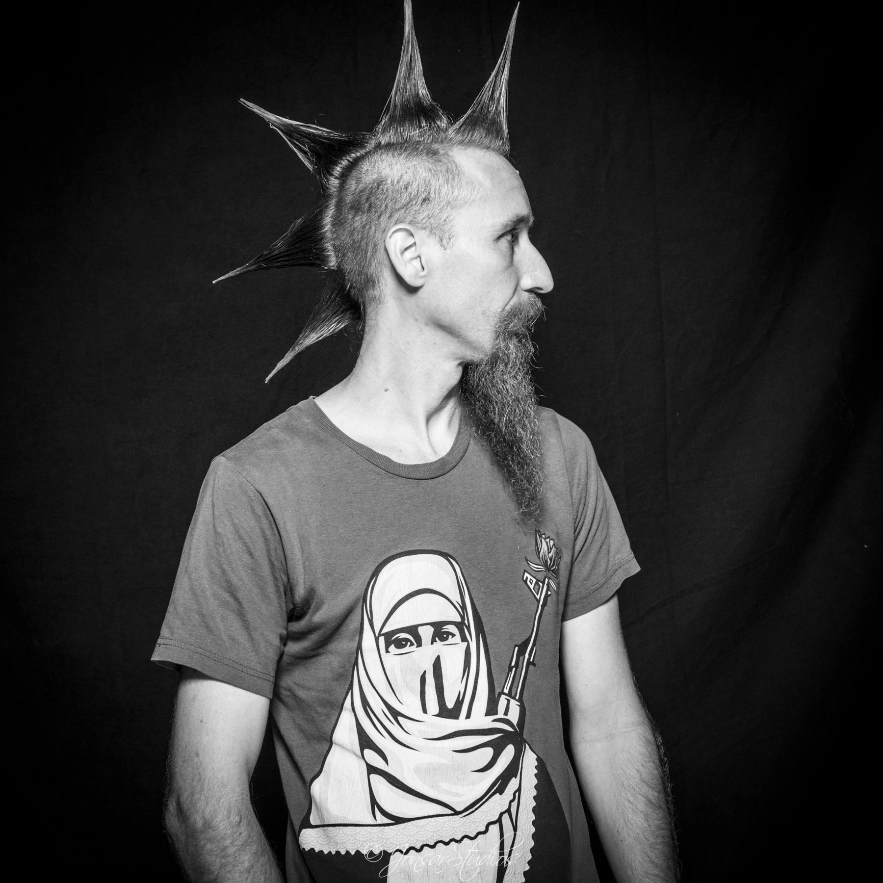 Profile of man with spiked mohawk and gun teeshirt, photographed on black background