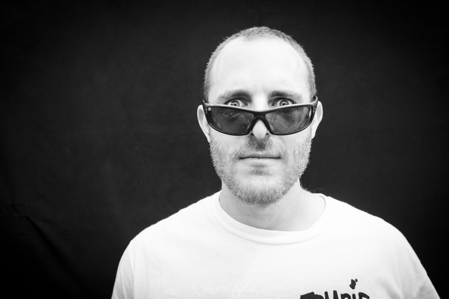 Portrait of man peering over sunglasses, photographed on black background