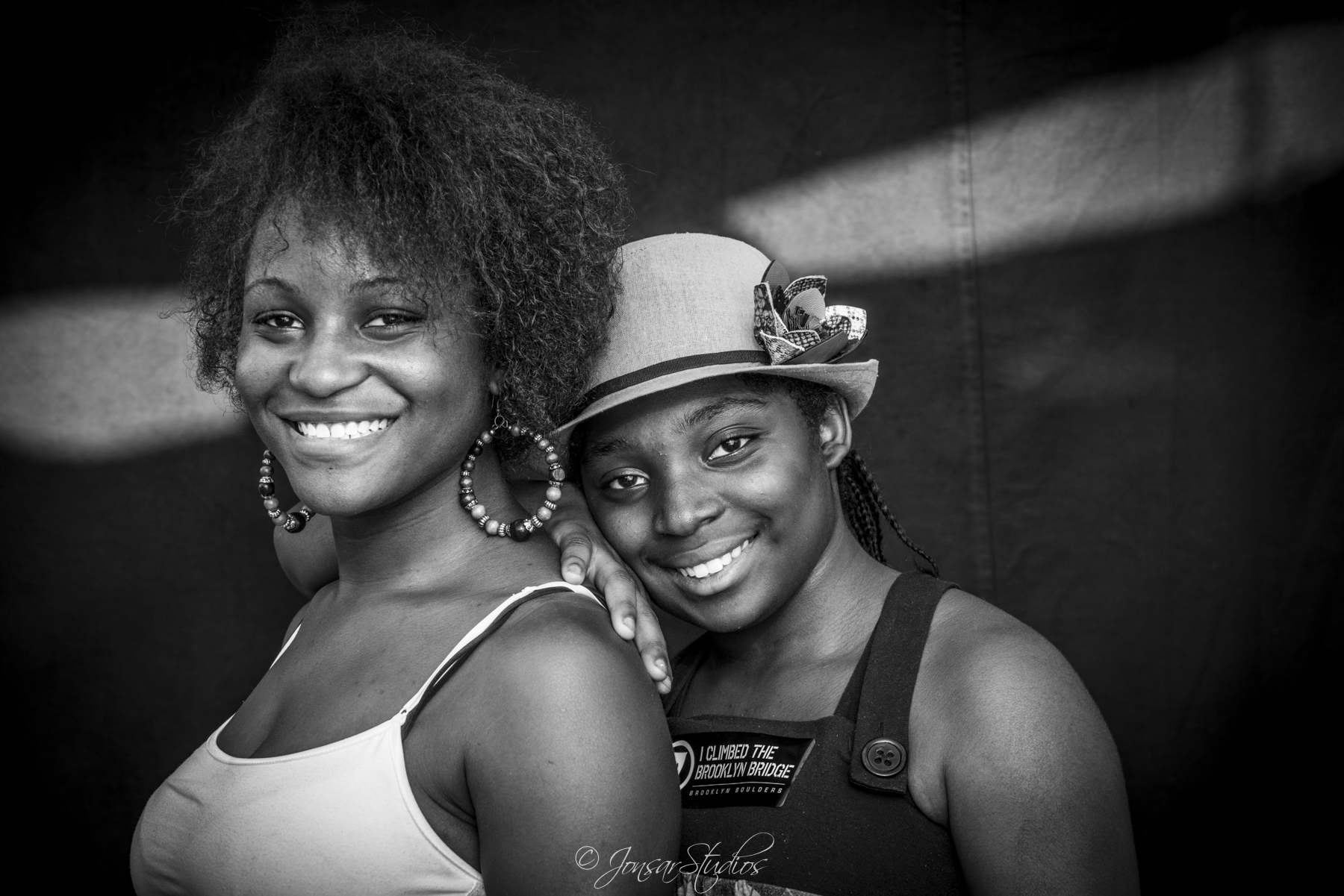 Smiling sisters photographed on black background