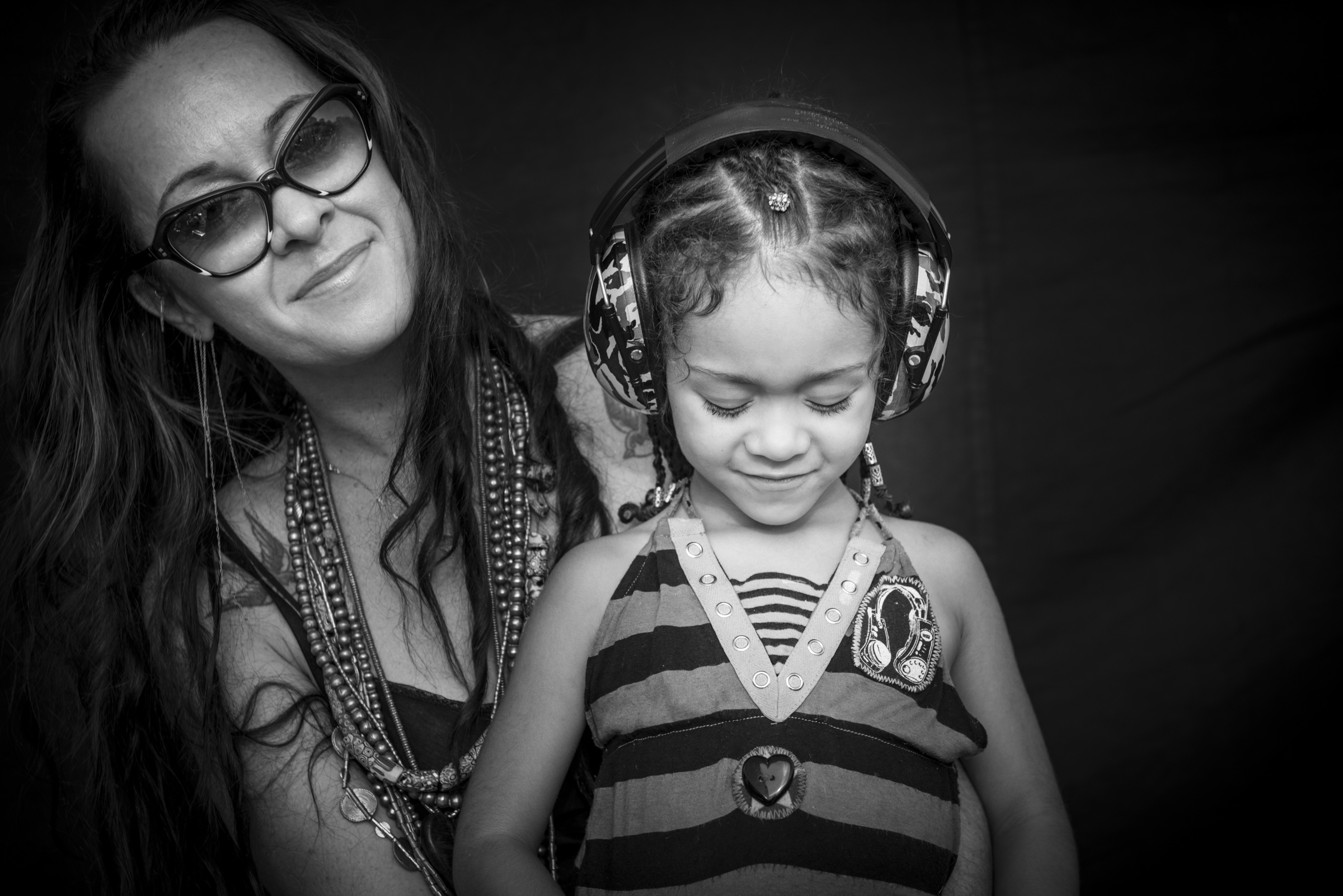 Mother with daughter in headphones photographed on black background