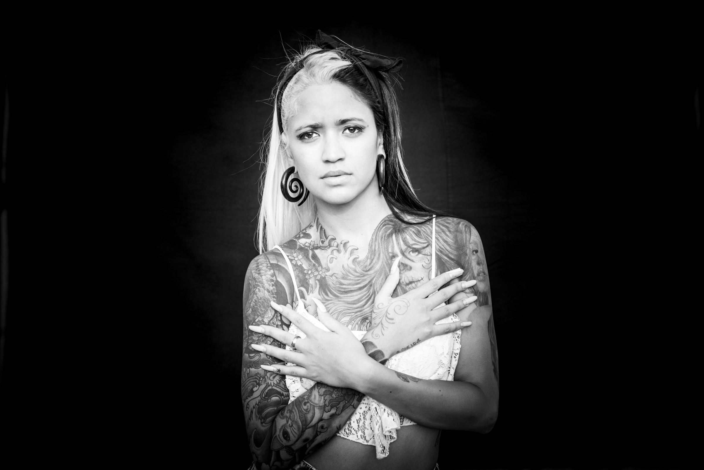 Woman with long nails and tattoos photographed on black background