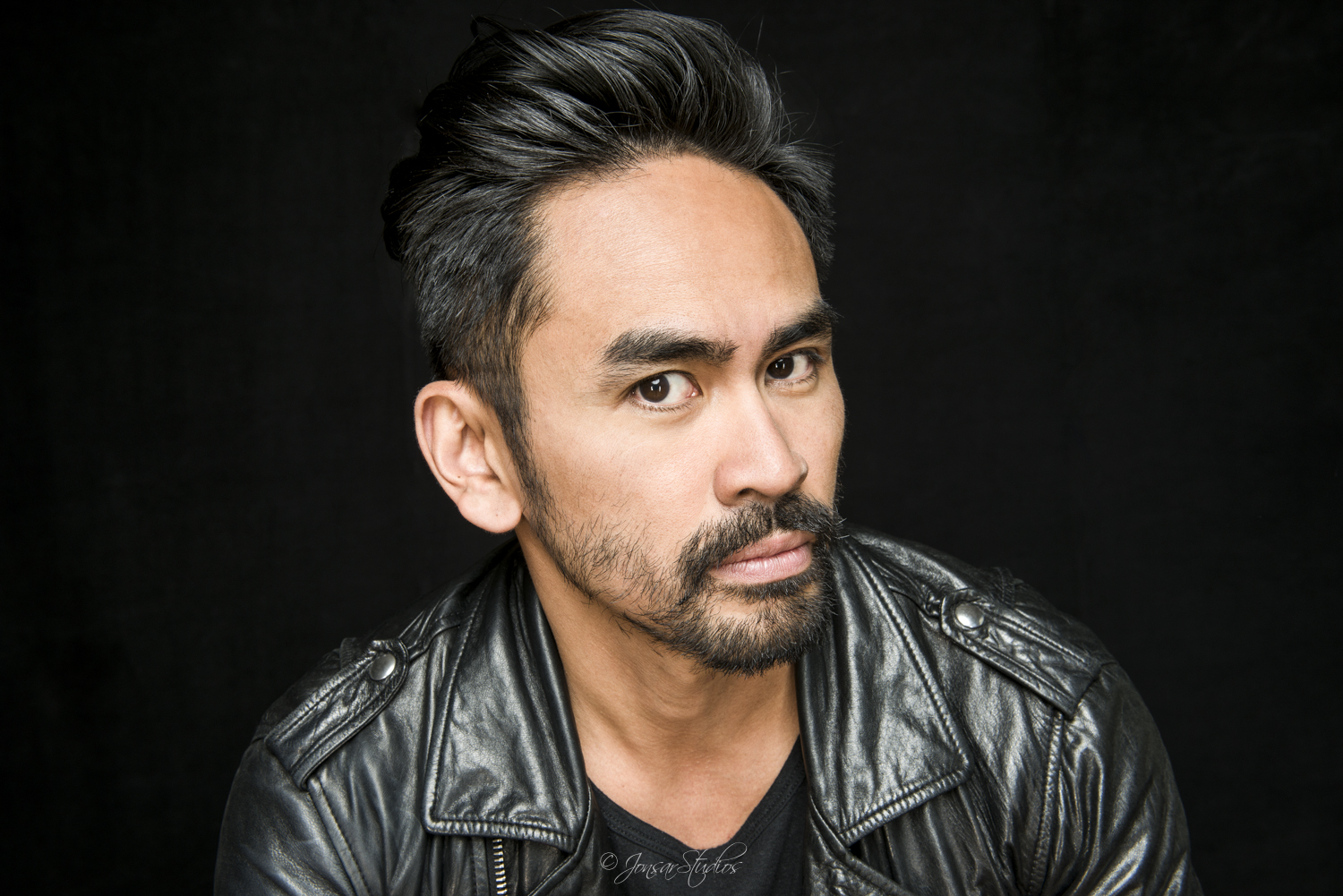 Portrait of man in leather jacket on black background