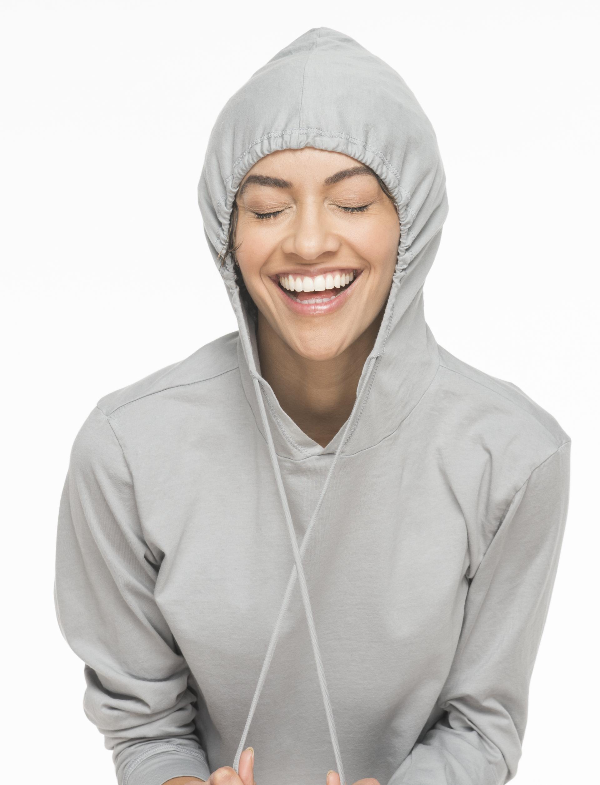Laughing girl with closed eyes, wearing hoodie.