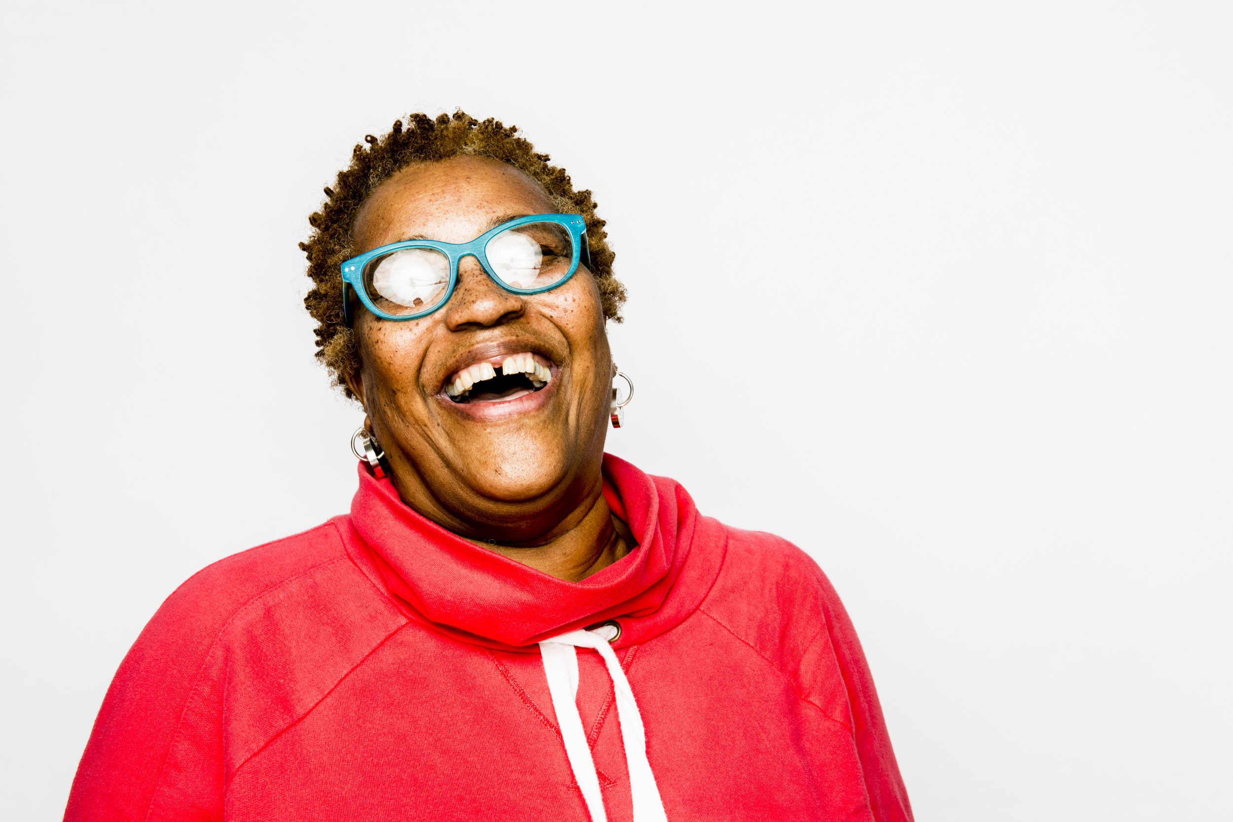 Gap-toothed woman smiling broadly on white background