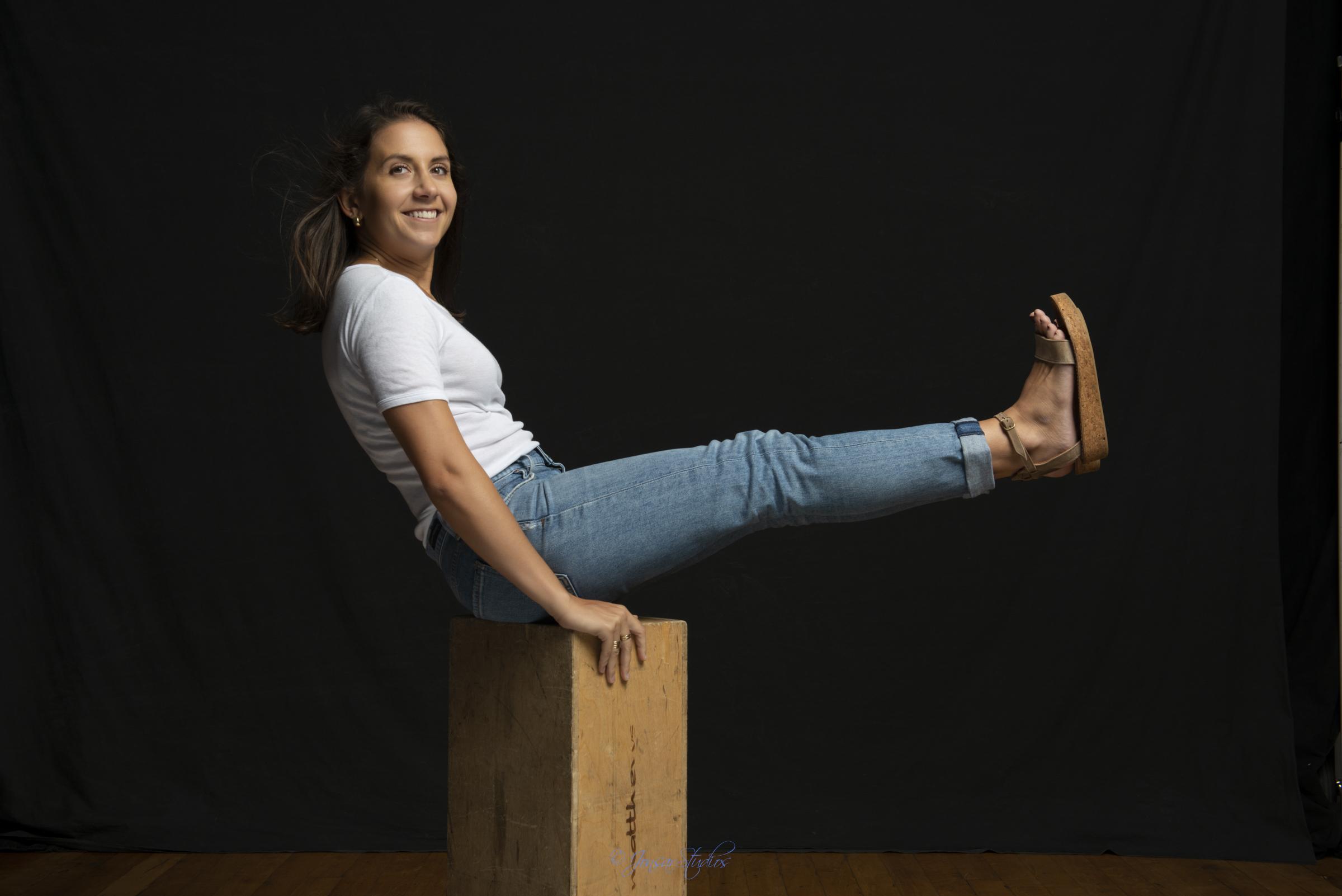 Color studio portrait of woman in jeans on apple box on black backdrop