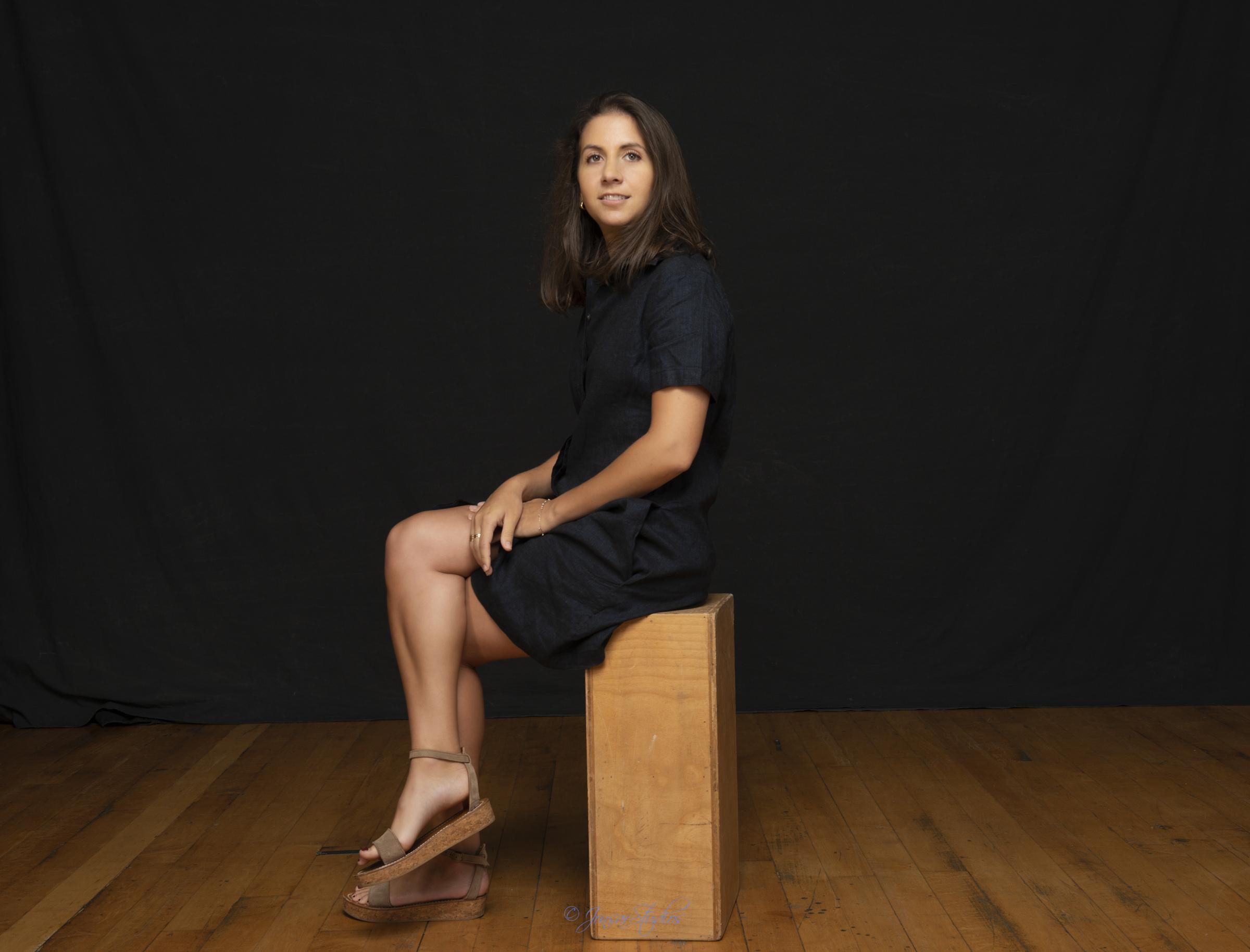Color studio portrait of woman seated on apple box on black backdrop