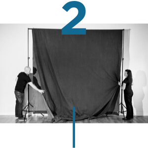Photo of Two People Adjusting Photo Backdrop on Stands