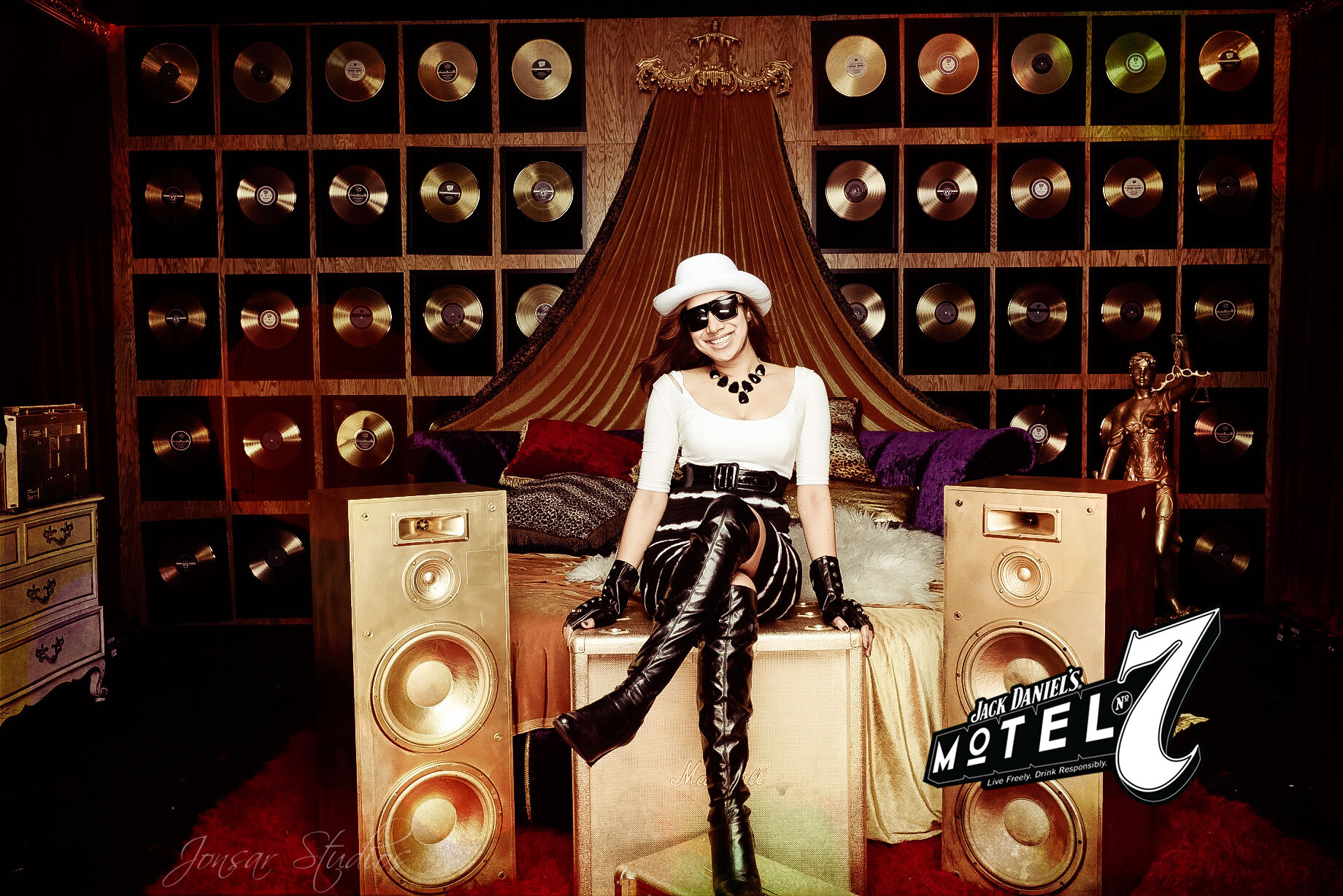Girl wearing knee high black boots in rockstar themed hotel room