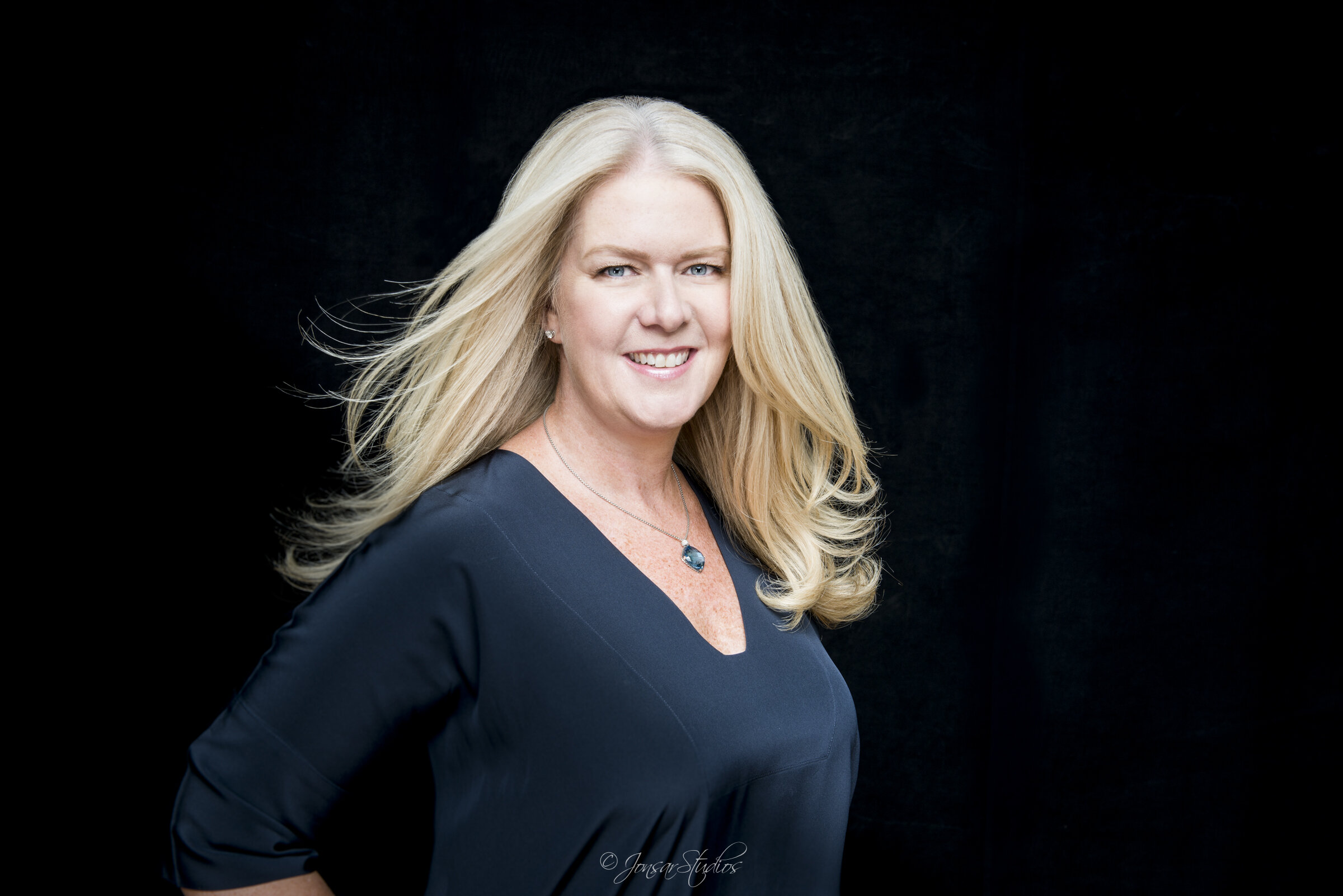 Color corporate portrait of blonde woman on black background