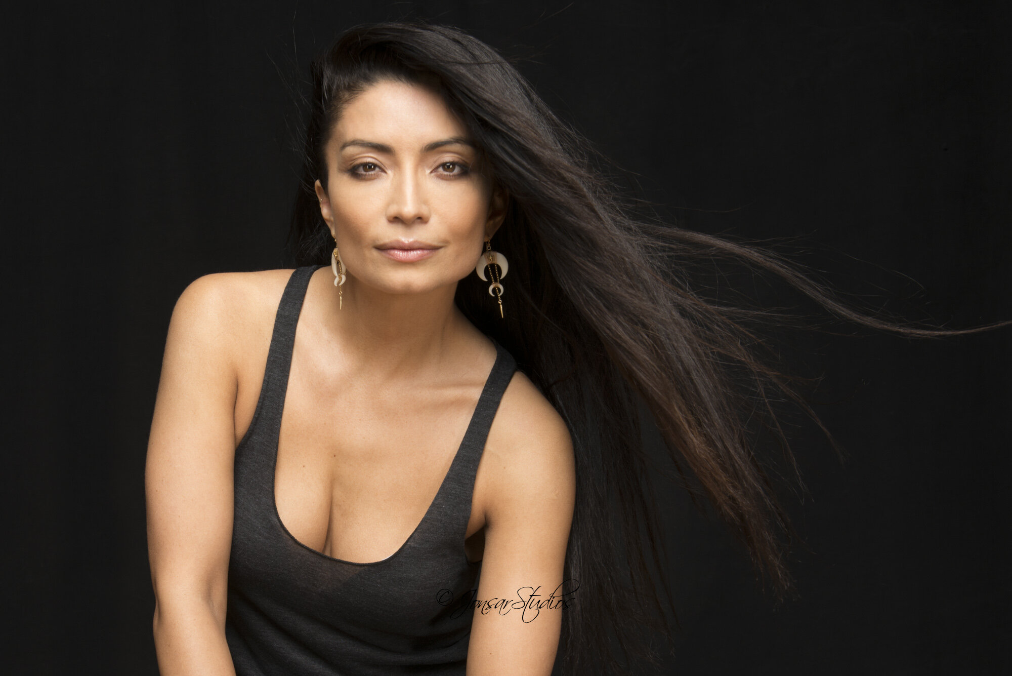 Color portrait of woman with long black hair on black background