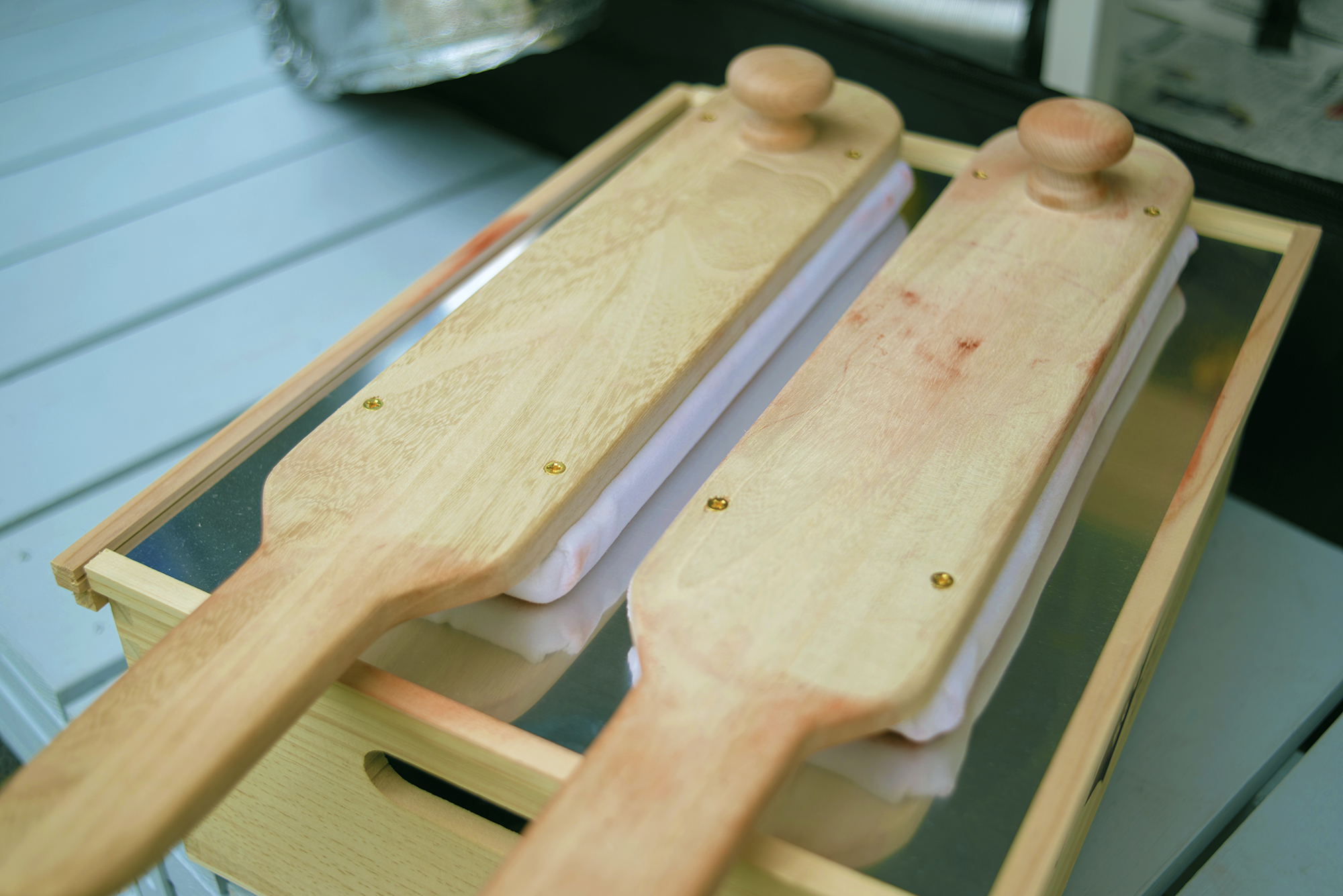 Hand-made buffing sticks to buff a silver plate for hours.  像が現れる銀板を数時間磨くためのハンドメイドのパドル と そのパドルを温める箱  상이 나타나는 은판을 몇 시간 동안 닦기 위한 핸드메이드 페달과 그 패달을 데우는 상자