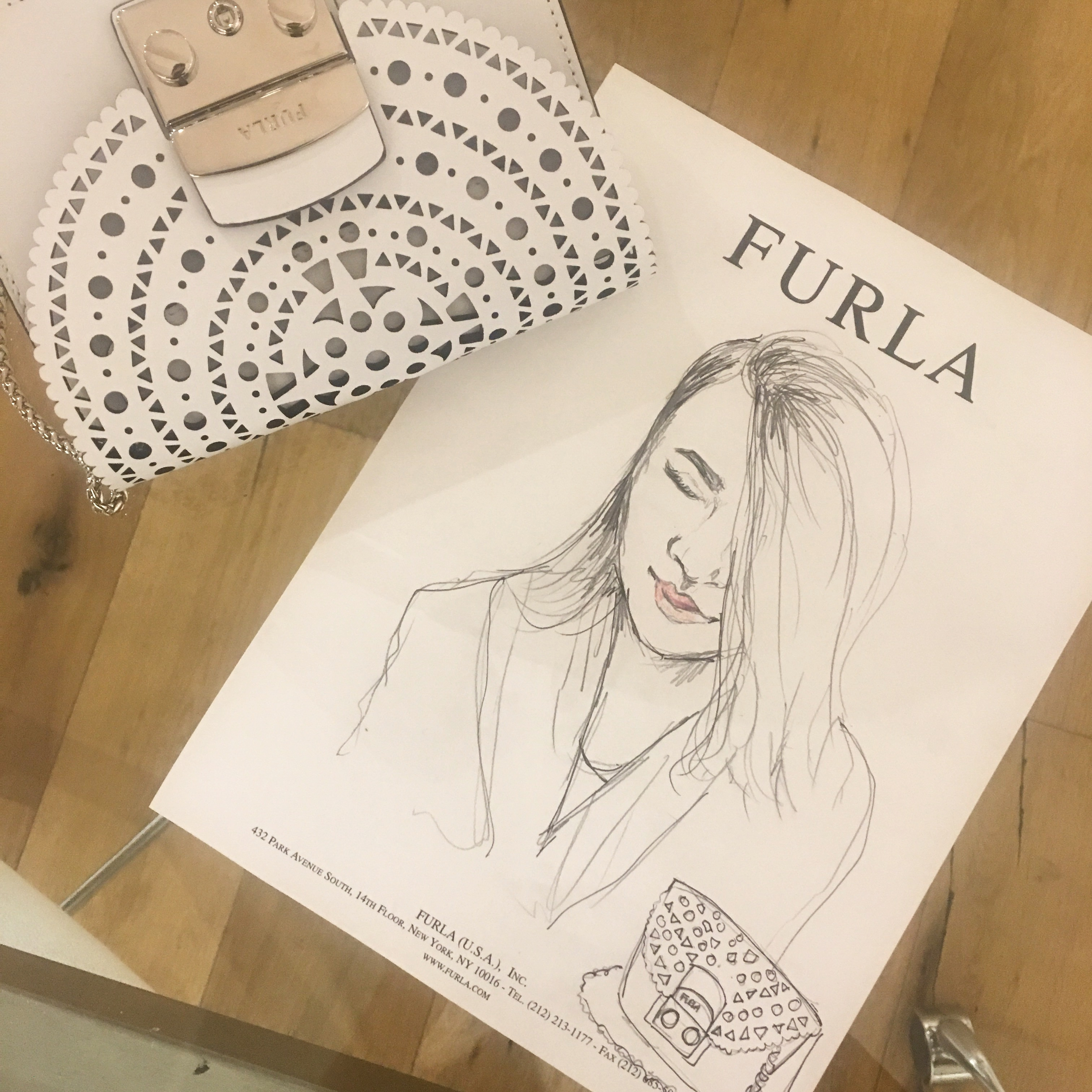 A live sketch of a fashion blogger at the Furla event in their showroom, featuring a handbag from their line.