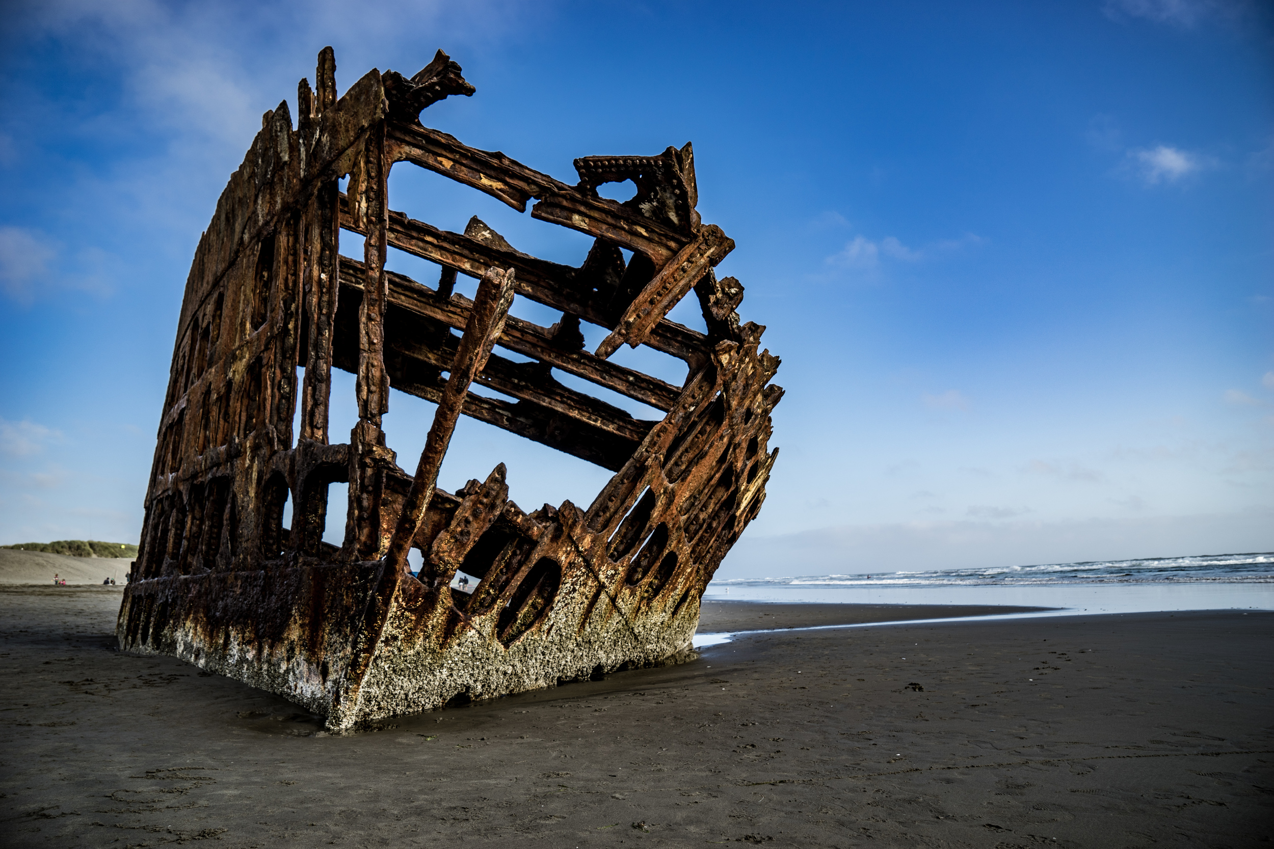 The remain of  Peter Iredale 's rusty bow and masts.  The ship was washed ashore in 1908 as it was bound for Portland from Mexico.  Thankfully, there were no casualties (Wikipedia).