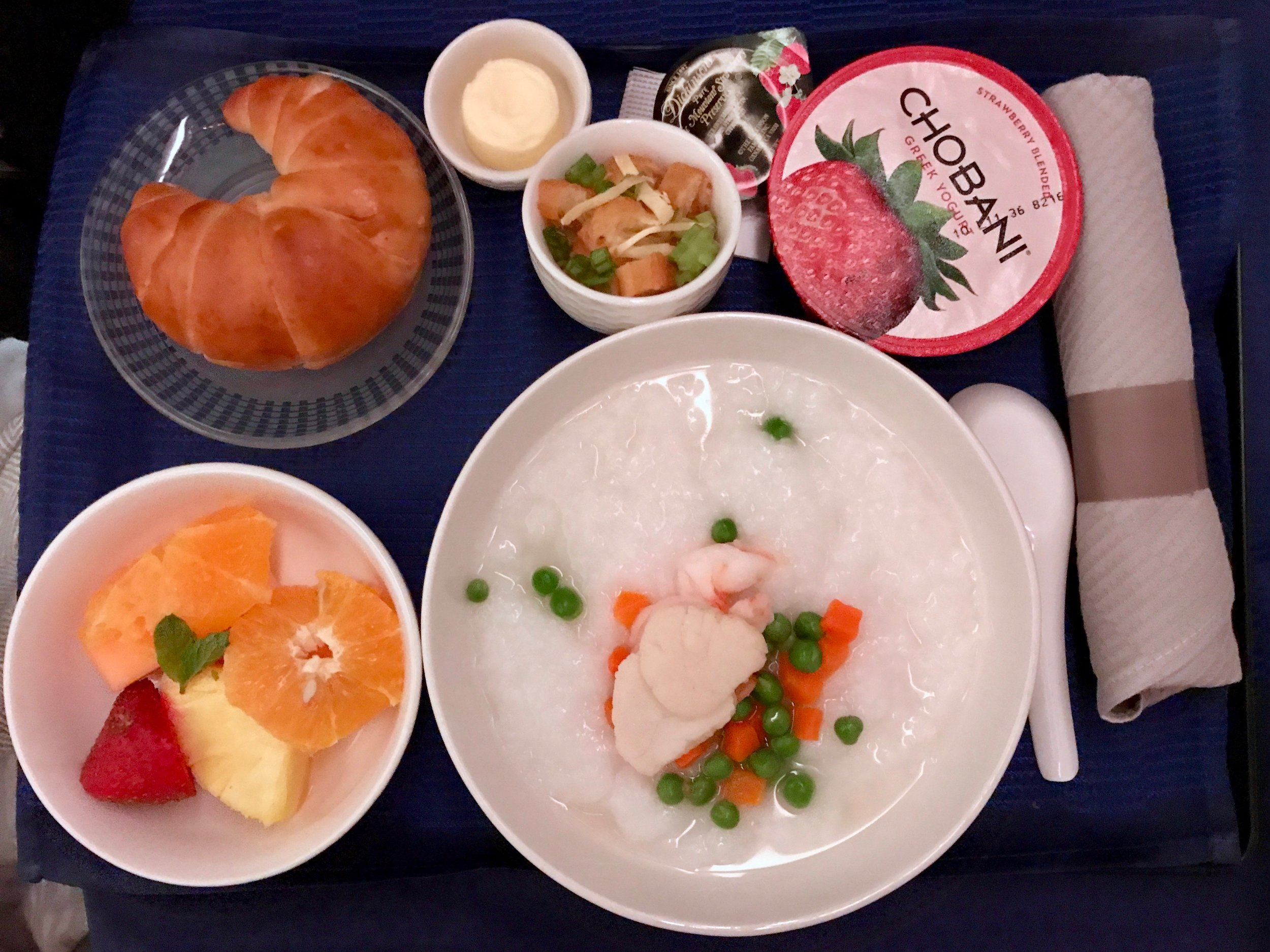Seafood congee and fresh fruits for breakfast.